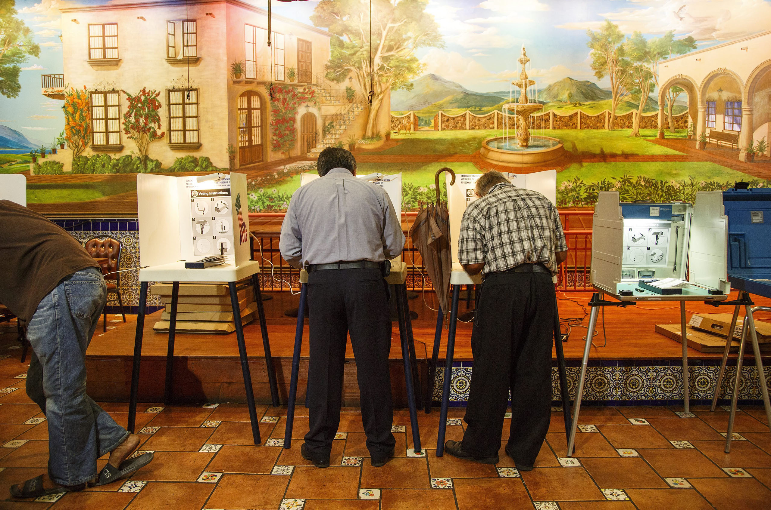 Voters cast their ballots under a mural depicting rural Mexico at the El Mercadito Mariachi restaurant polling location on Nov. 8, 2016, in Los Angeles.