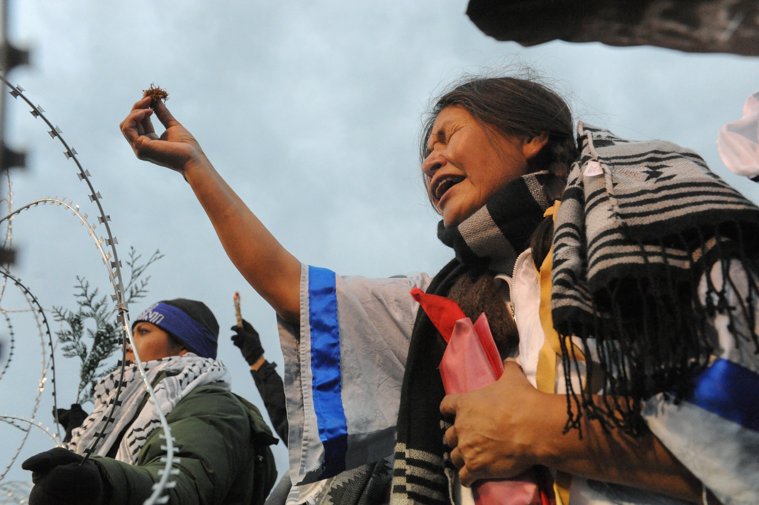 Cheryl Angel offers ceremonial tobacco on Backwater Bridge during a protest against plans to pass the Dakota Access pipeline near the Standing Rock Indian Reservation, near Cannon Ball, North Dakota, on Nov. 27, 2016.