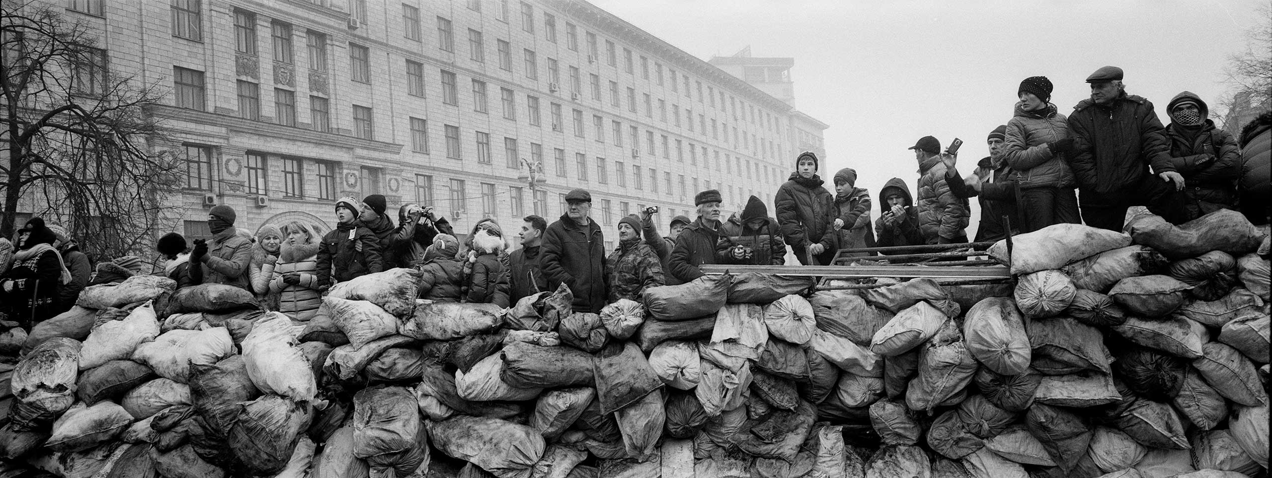 Ukrainian civilians stand behind a barricade as they watch at Riot police lines near the Maidan square in Kiev, 2014. From the                               series: Barricades, Kiev, Ukraine, 2014.