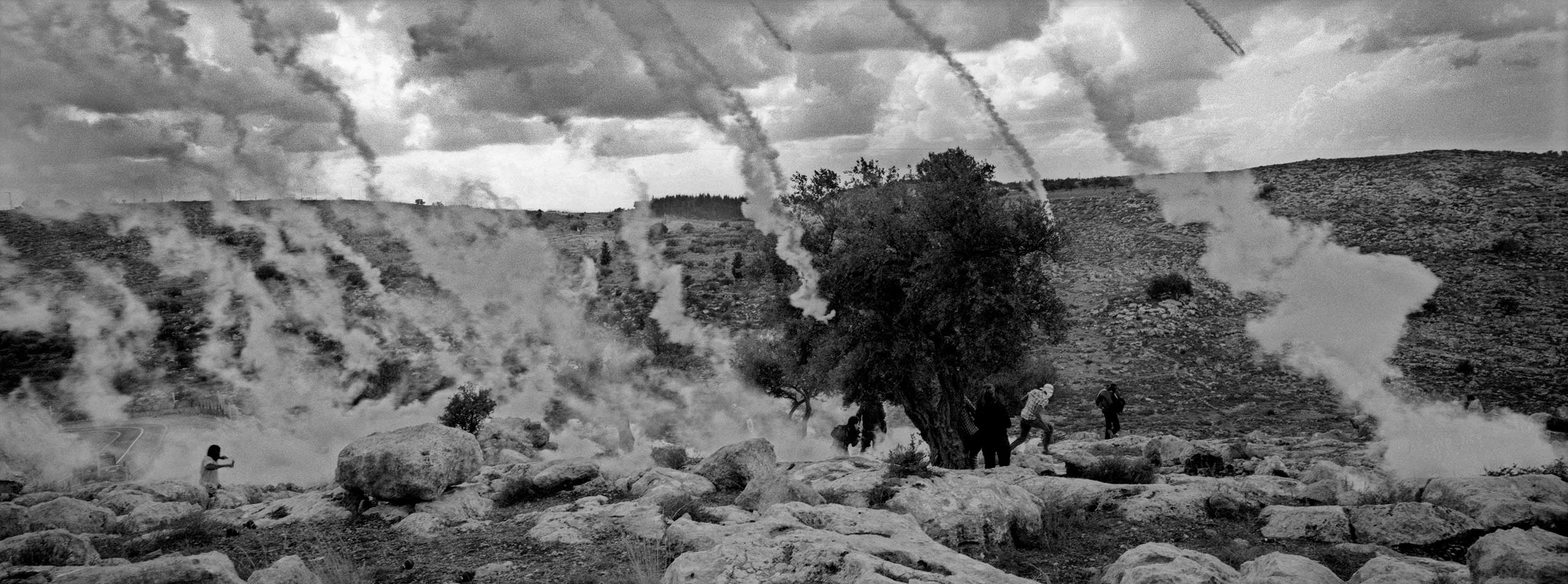 Protestor running from tear gas during riots in the Palestinian village of Nilin in the West Bank. From the                                series: Barricades,                               2010