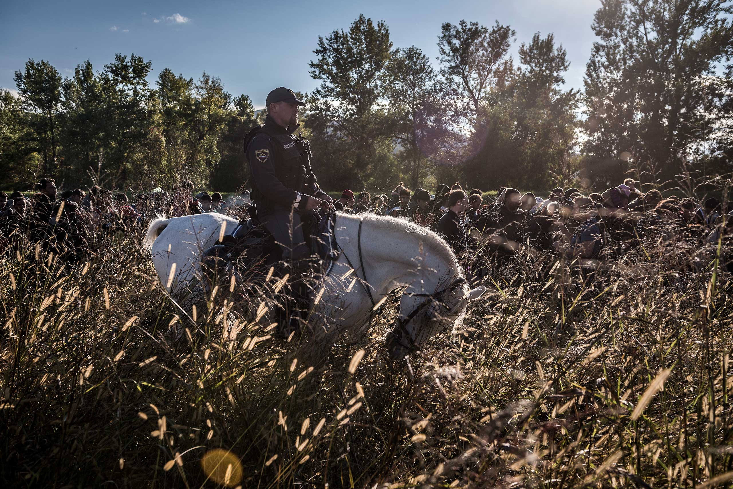 Police on horses escort hundreds of migrants after they crossed from Croatia in Dobova, Slovenia, Tuesday October, 20, 2015.