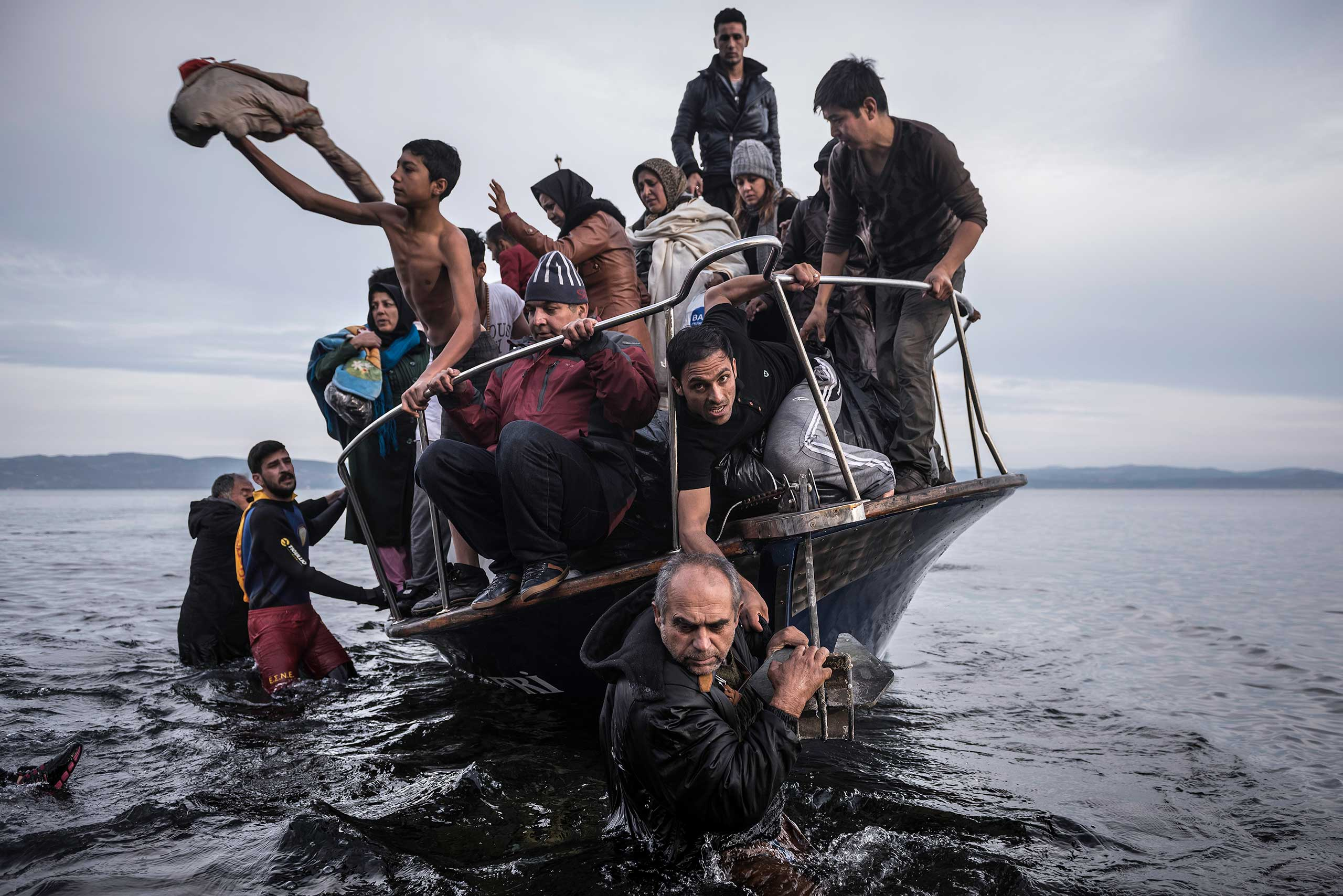 Migrants arrive by a Turkish boat near the village of Skala, on the Greek island of Lesbos. The Turkish boat owner delivered some 150 people to the Greek coast and tried to escape back to Turkey; he was arrested in Turkish waters.                                Series: Europe Migration Crisis. November 16, 2015.