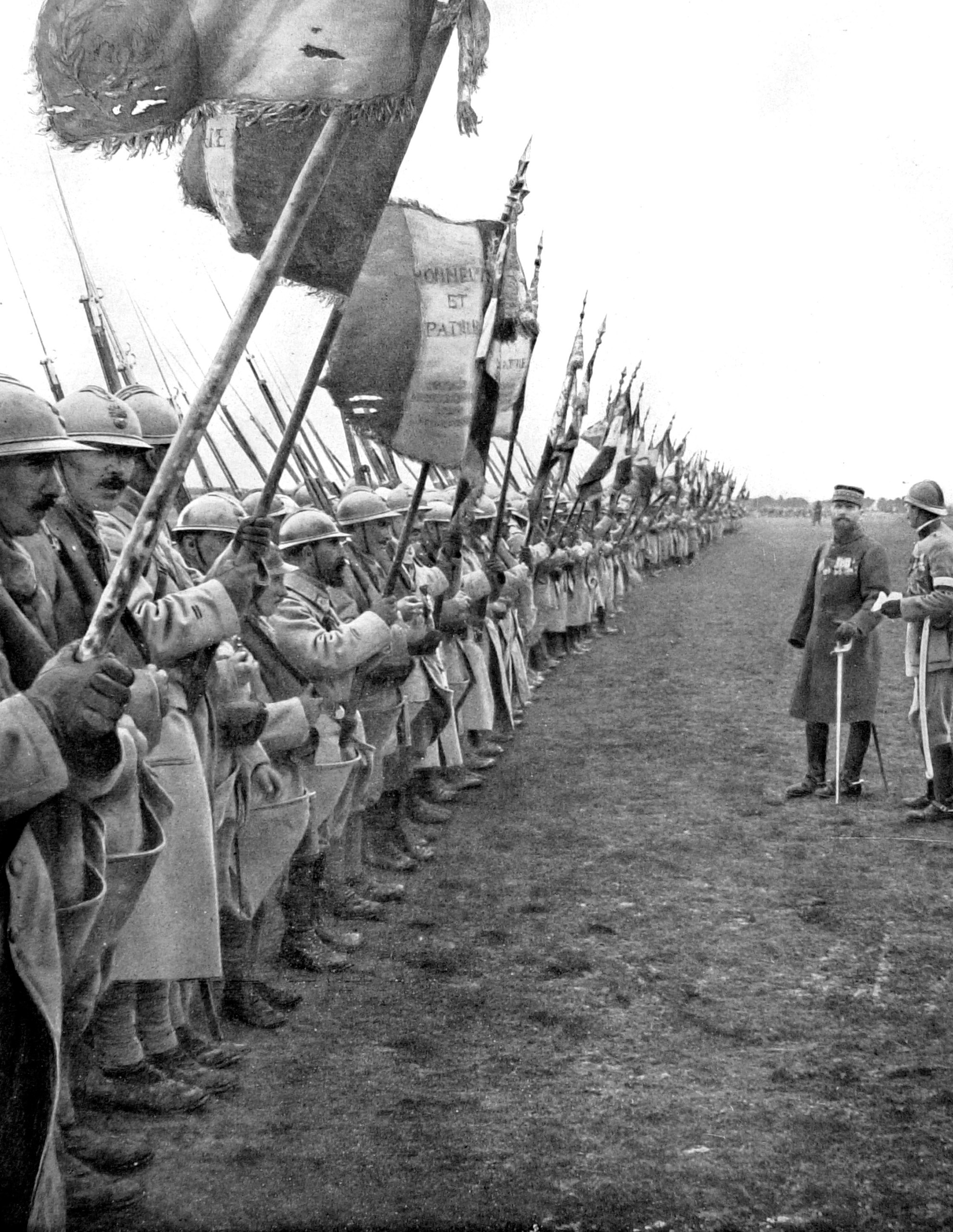 General Gouraud has gathered flags of all regiments of his army to salute a division who won battles in Verdun. 1916.