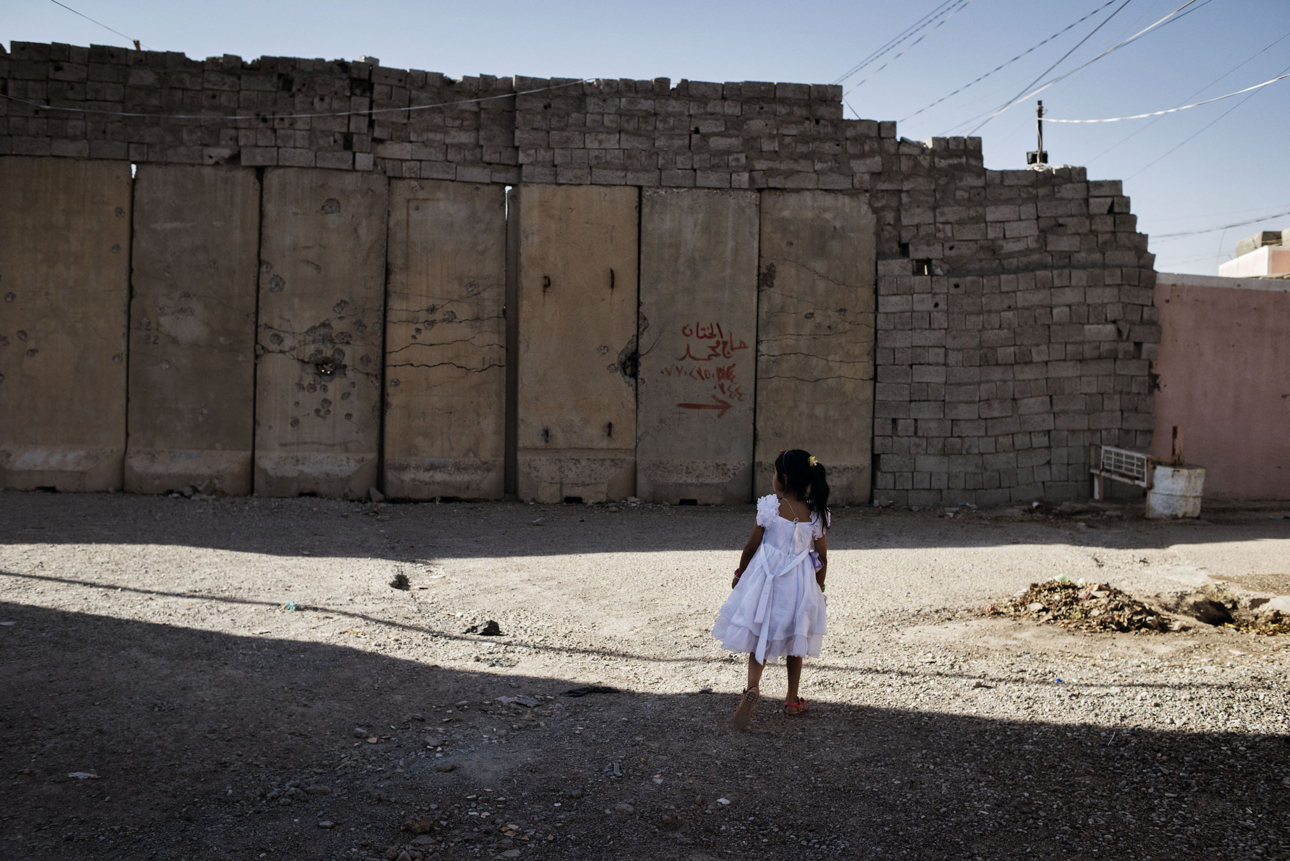 A young girl walks by a wall in the town of Tuz Khurmatu, northern Iraq, May 20, 2016. Walls have been installed in the city as a result of recent fighting between rival Kurdish and Shiite Turkmen factions. The deadly clashes signaled tension among among two groups nominally united in the broader fight against ISIS.From  Yuri Kozyrev: On the Front Lines of the War Against ISIS