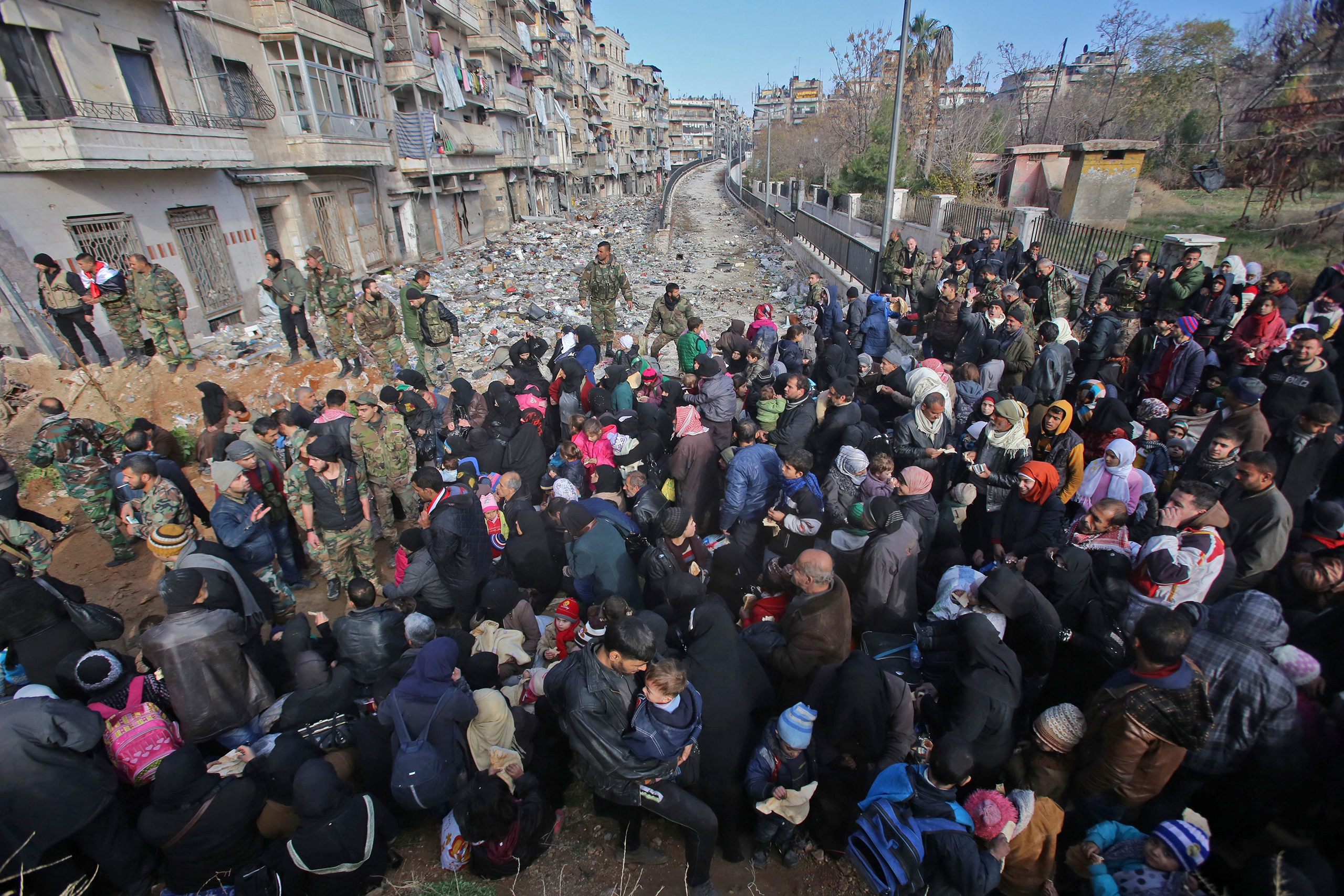 Residents fleeing the violence gather at a checkpoint, manned by pro-government forces, in the Maysaloun neighborhood of Aleppo on Dec. 8, 2016.