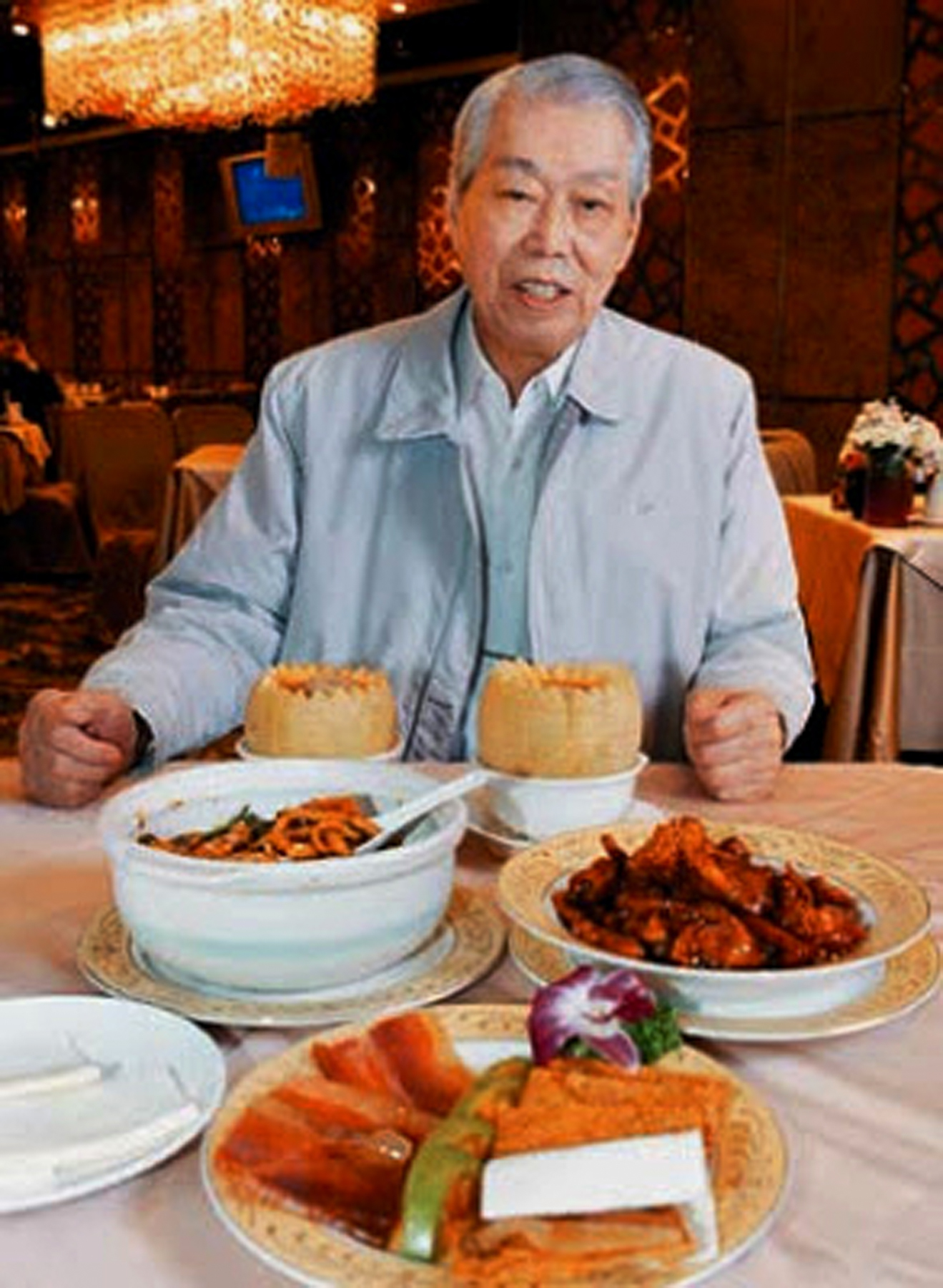 In this 2008 photo, chef Peng Chang-kuei poses for a photo as he is seated at a table in his restaurant Peng's Garden in Taipei. The chef, who has been credited with inventing General Tso's chicken, a world-famous Chinese food staple that is not served in China, died in Taiwan on Nov. 30 at the age of 98
