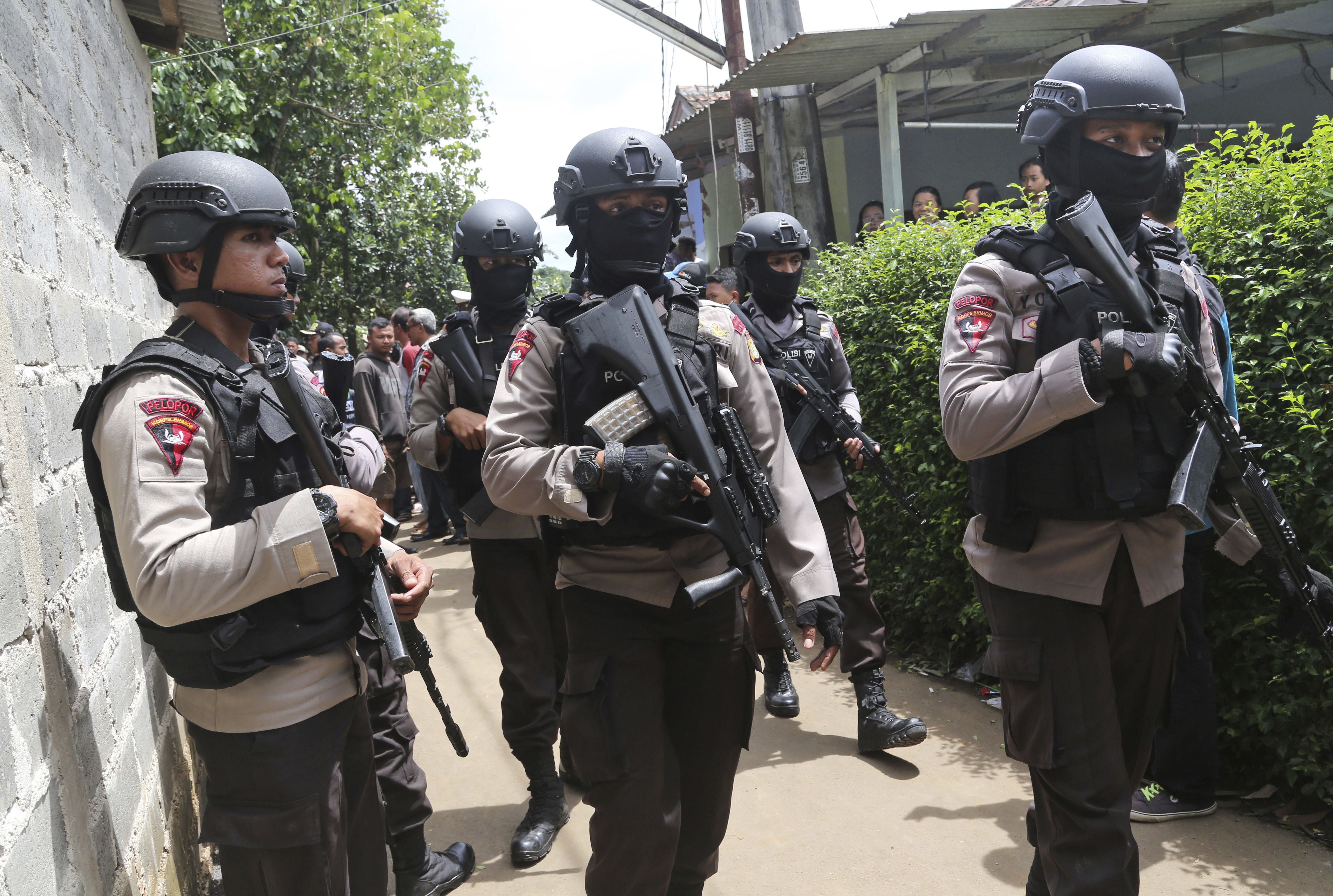 Police officers stand guard at a residential neighborhood in Tangerang, outside Jakarta, where police conducted a raid on a house used by suspected militants, on Dec. 21, 2016