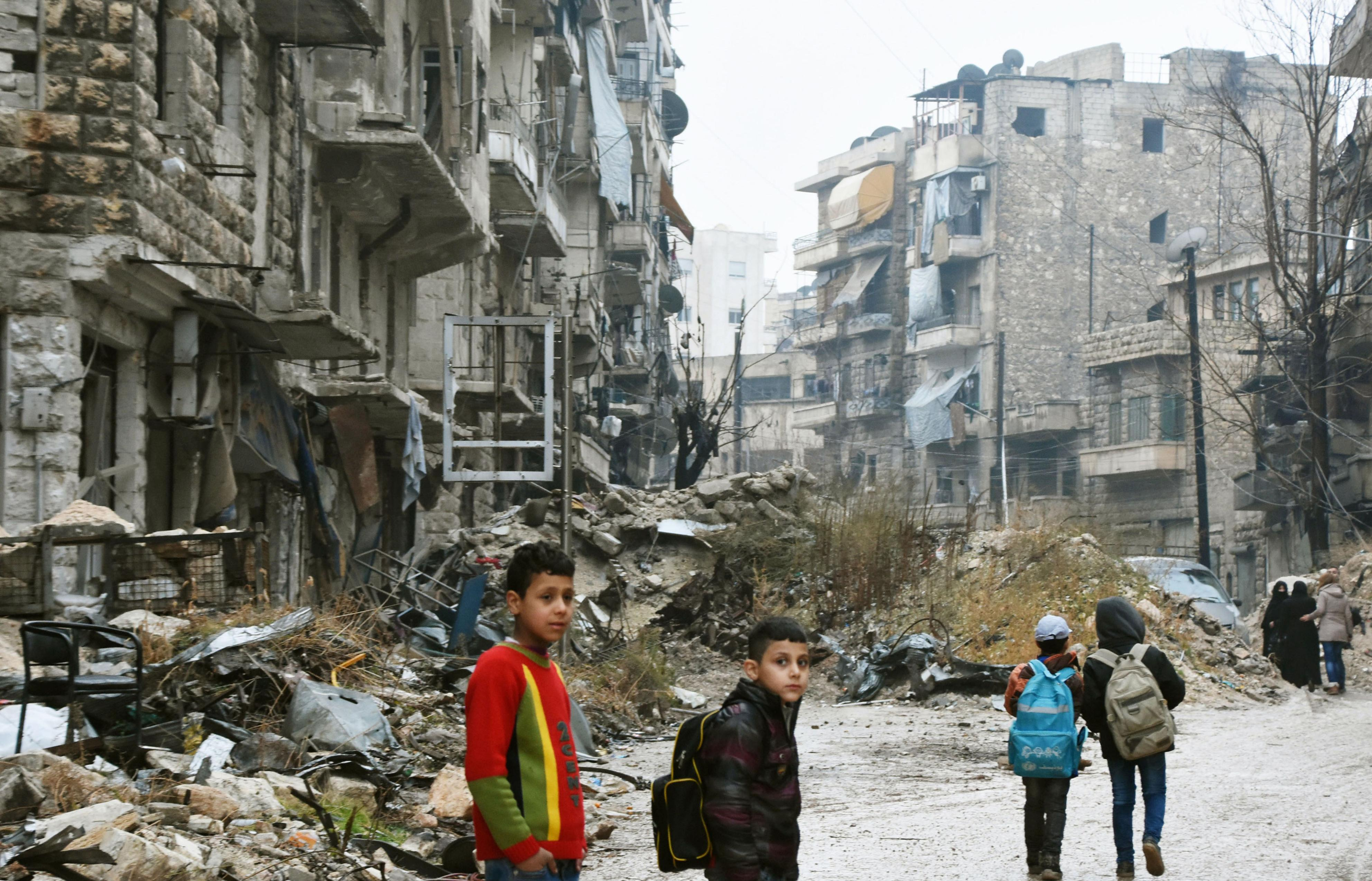Children walk in a devastated area in the northern Syria city of Aleppo on Dec. 13, 2016, as troops loyal to the government of President Bashar al-Assad seemed poised to take complete control of the city that had been ruled by rebels. (Kyodo)