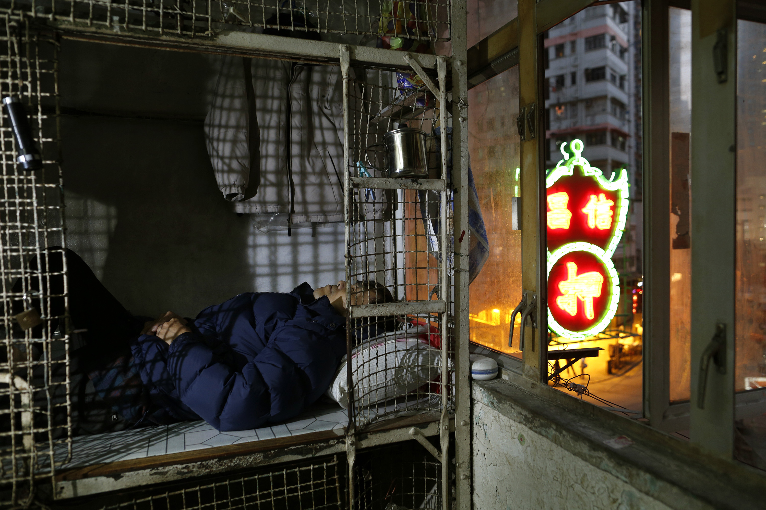In this Jan. 25, 2013, photo, 62-year-old Cheng Man-wai lays in his cage, measuring 16 sq. ft., which he calls home, in Hong Kong