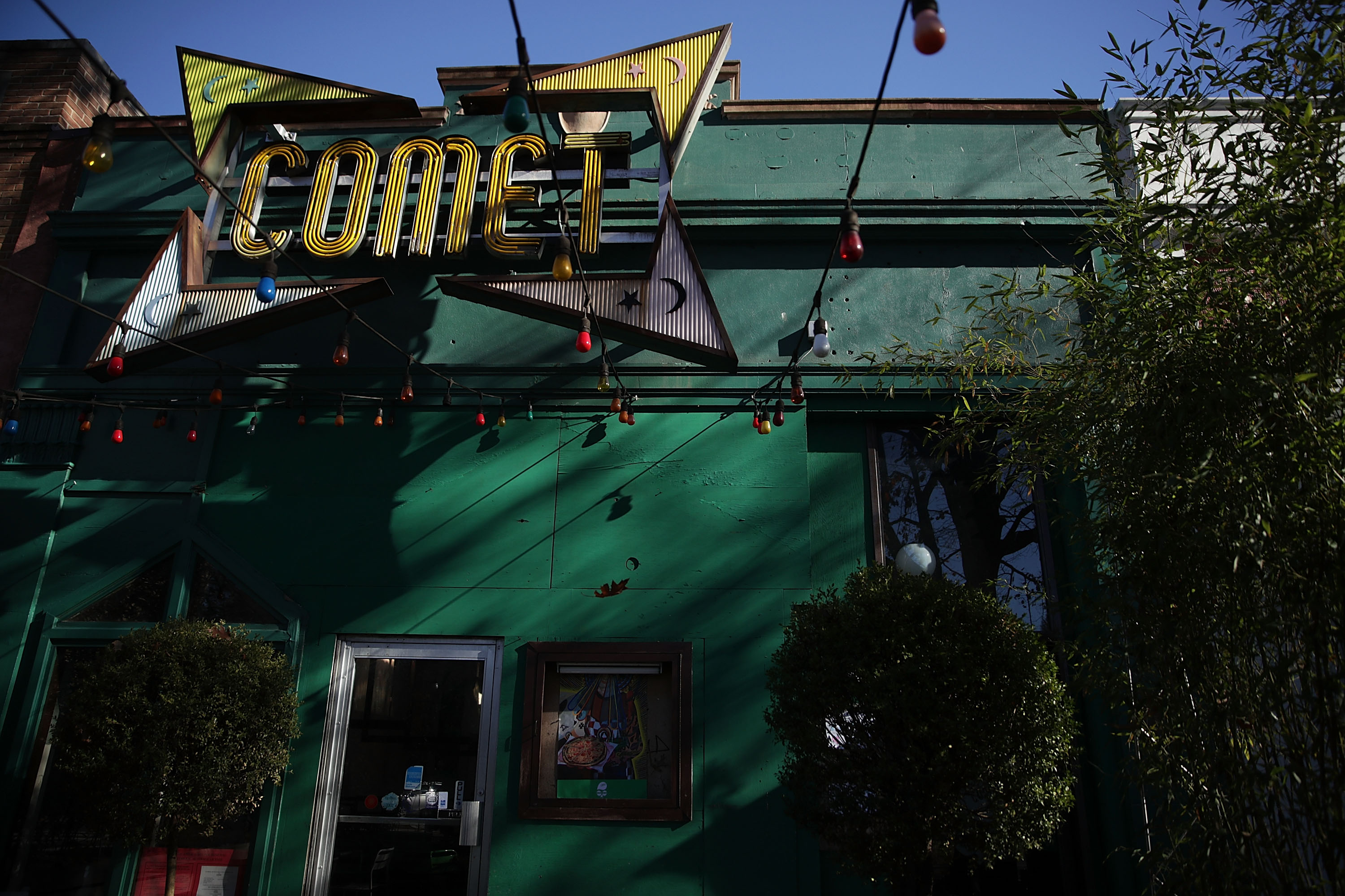 The sign and front entrance of Comet Ping Pong pizzeria are seen Dec. 5, 2016 in Washington, D.C. A man was arrested Sunday after walking into the pizzeria and discharging a rifle, claiming he was  self-investigating  an online conspiracy theory about a pedophilia ring being run by high-ranking Democrats, including Hillary Clinton.