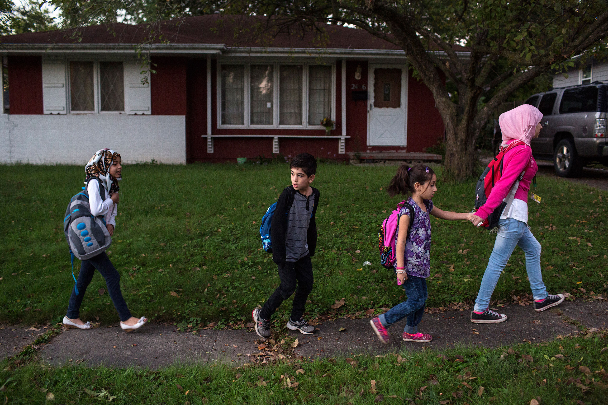 Sedra walks her brother Mutaz, sister Hala (with pink backpack) and a friend to their school-bus stop in the family's neighborhood in Des Moines, Sept. 19, 2016.From  A Syrian Family Finds a New Home in Iowa