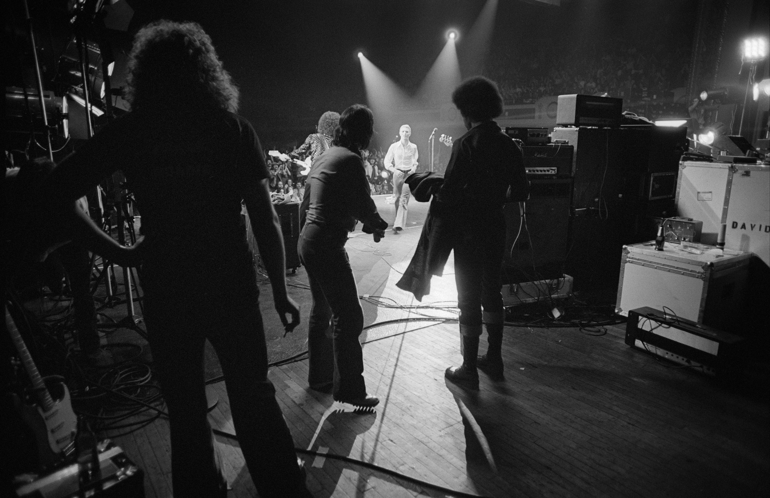 Bowie runs off stage towards his crew, during a stop on the Isolar Tour at Olympia Stadium in Detroit, Michigan, 1976.