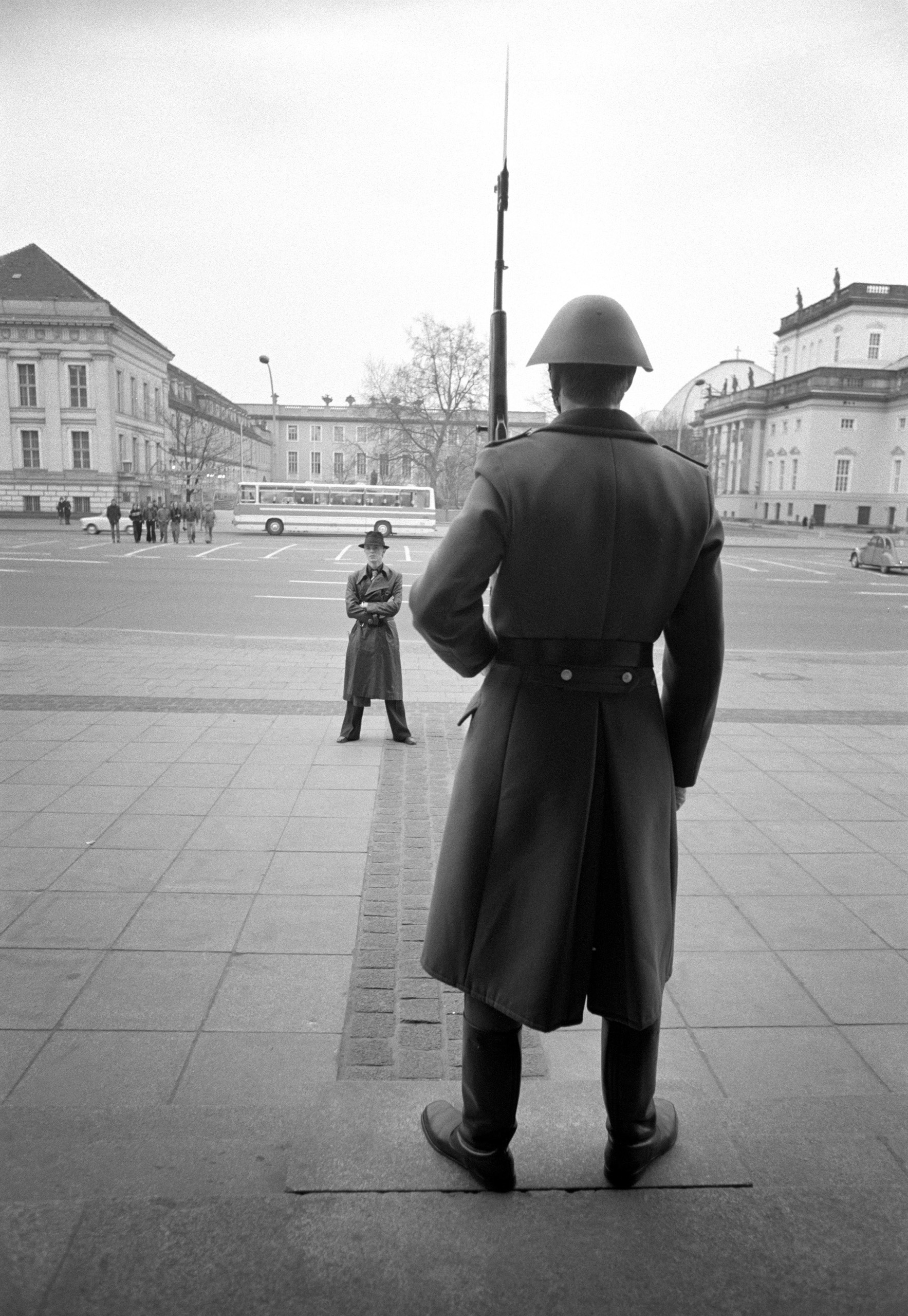 Bowie pauses in front of an armed guard, during a walk around East Berlin, 1976.