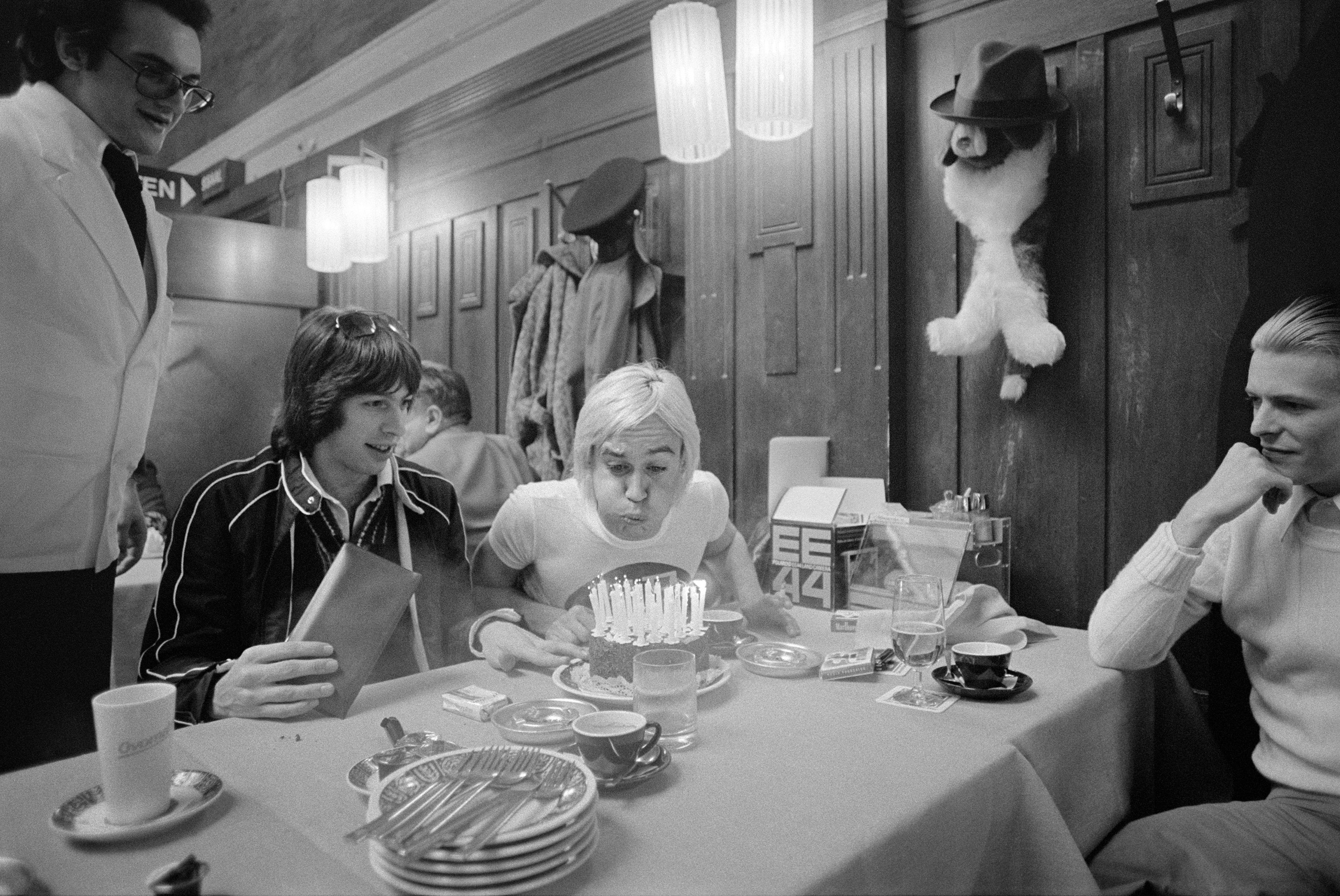 Iggy Pop blows out the candles on his birthday cake as Bowie and Pat Gibbons look on at a restaurant in Basel, Switzerland train depot prior to departing for the Soviet Union.