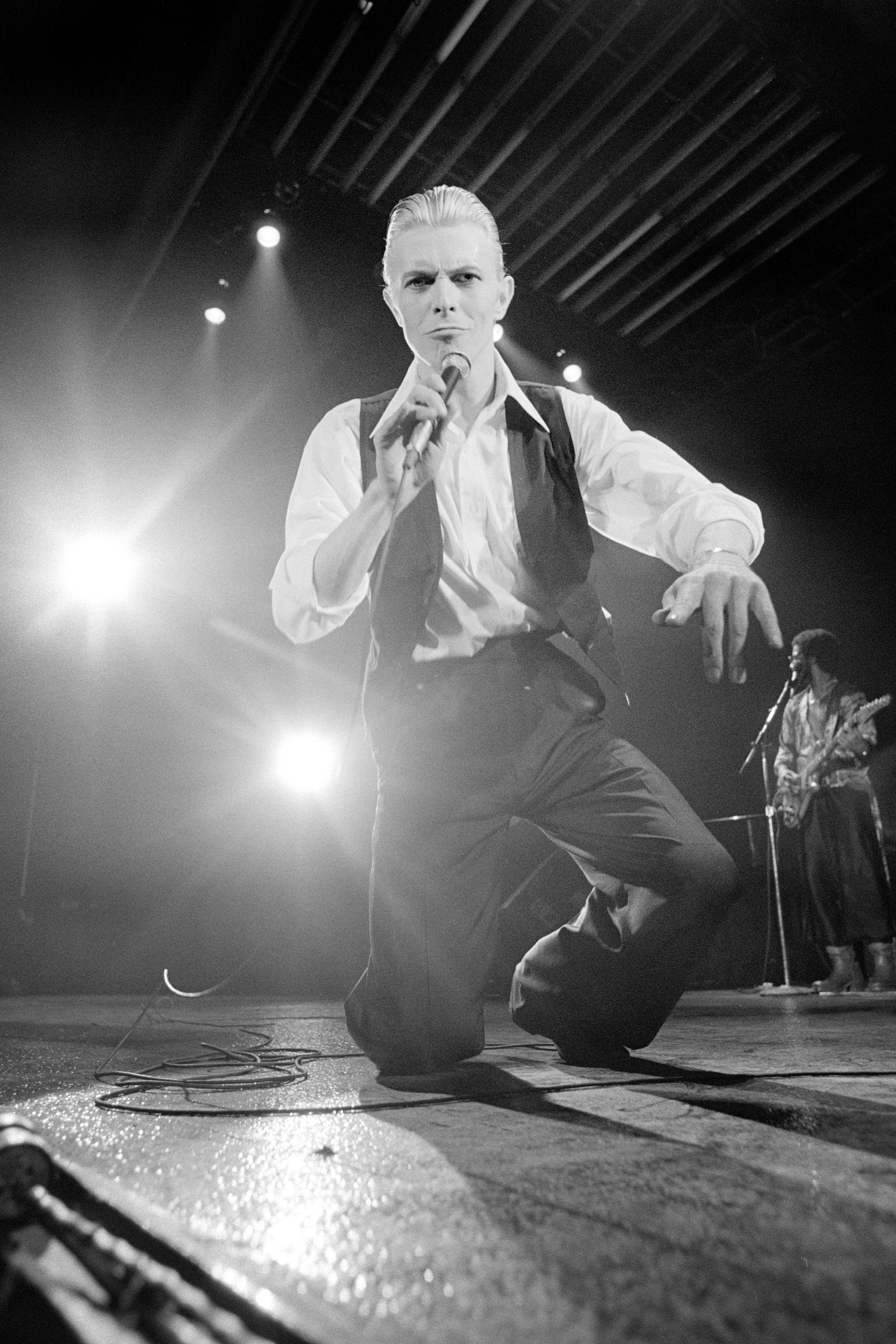 Bowie performing on stage prepares to make a lunge into Kent's camera.