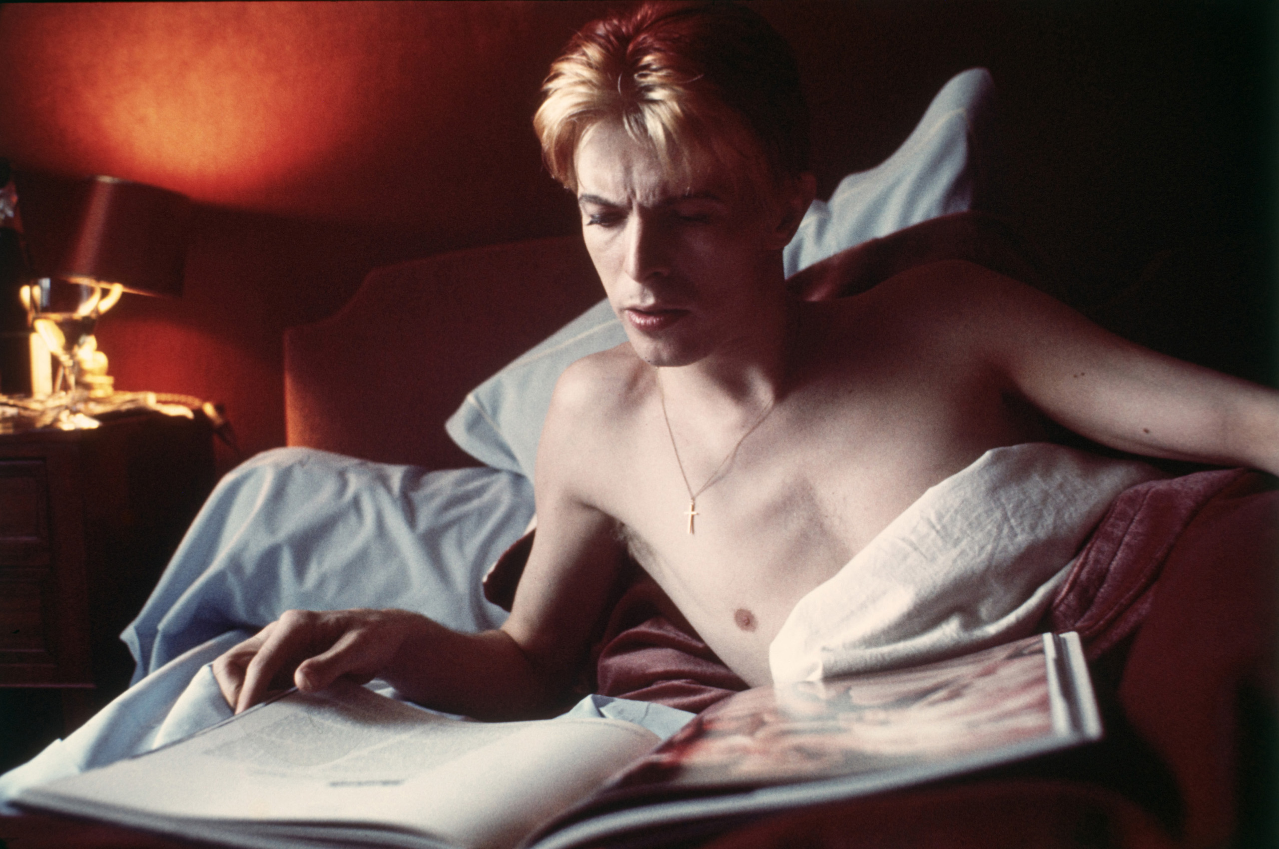 Bowie reading in bed at L'Hotel in Paris.