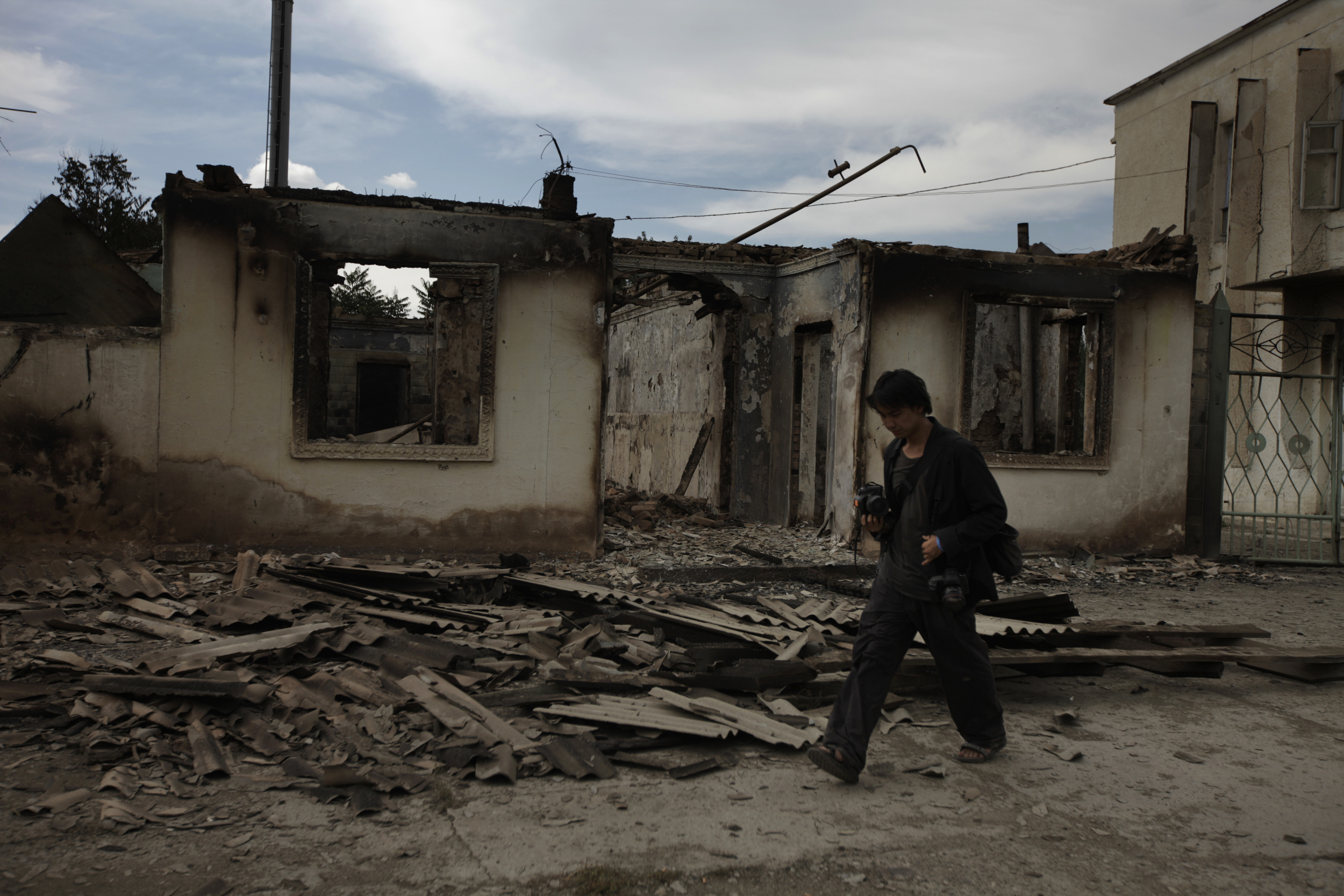 Ed Ou photographs a burned home after ethnic Kyrgyz mobs rampaged through minority Uzbek enclaves, burning homes and businesses in Shark, Kyrgyzstan.