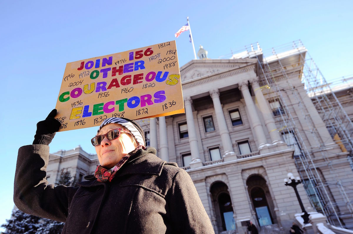 Amber Dahlin holds a sign urging the electors to vote their conscience outside the Colorado Capitol building in Denver on Dec. 19, 2016