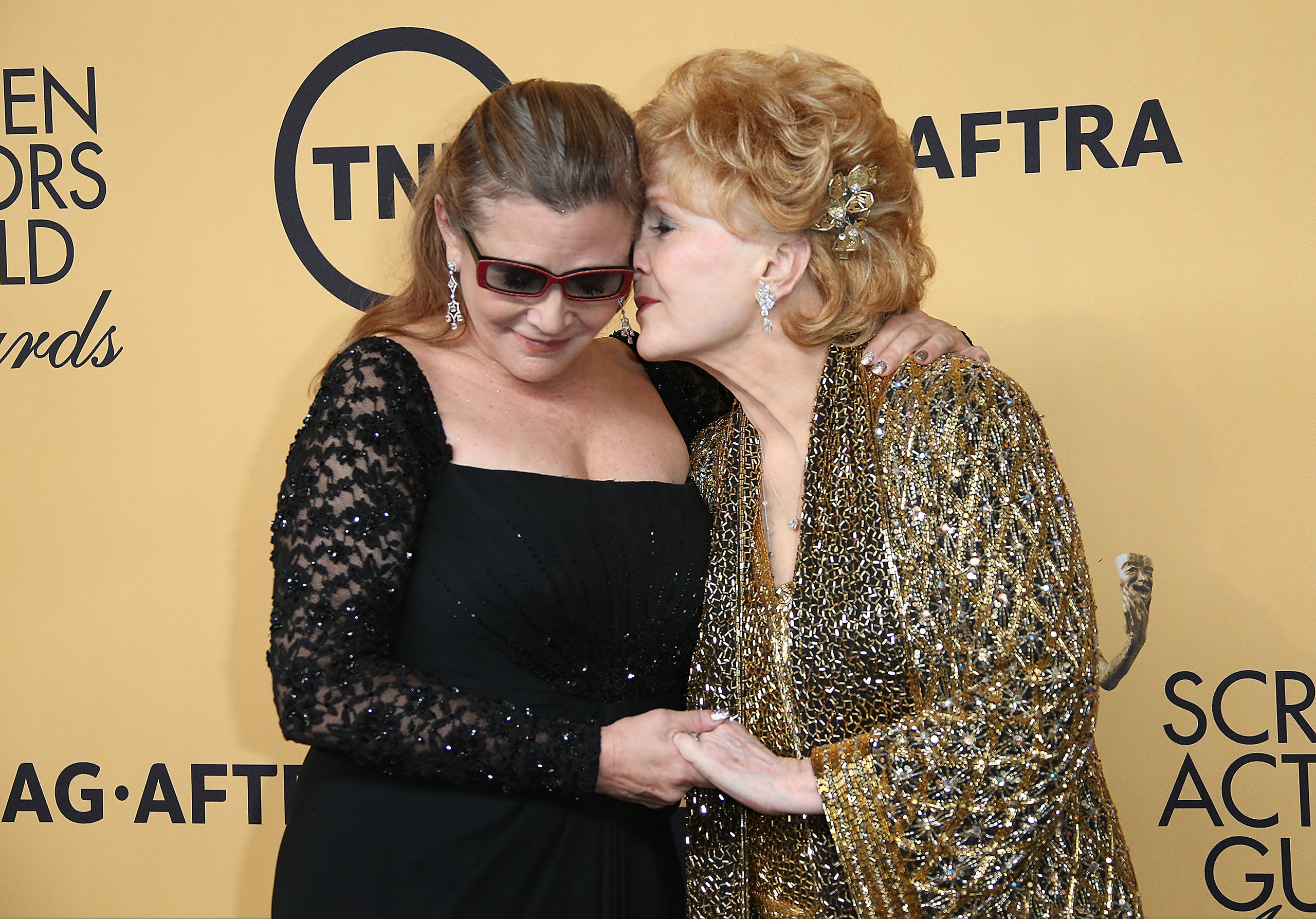 Carrie Fisher and Debbie Reynolds pose in the press room at TNT's 21st Annual Screen Actors Guild Awards at The Shrine Auditorium on Jan. 25, 2015 in Los Angeles.
