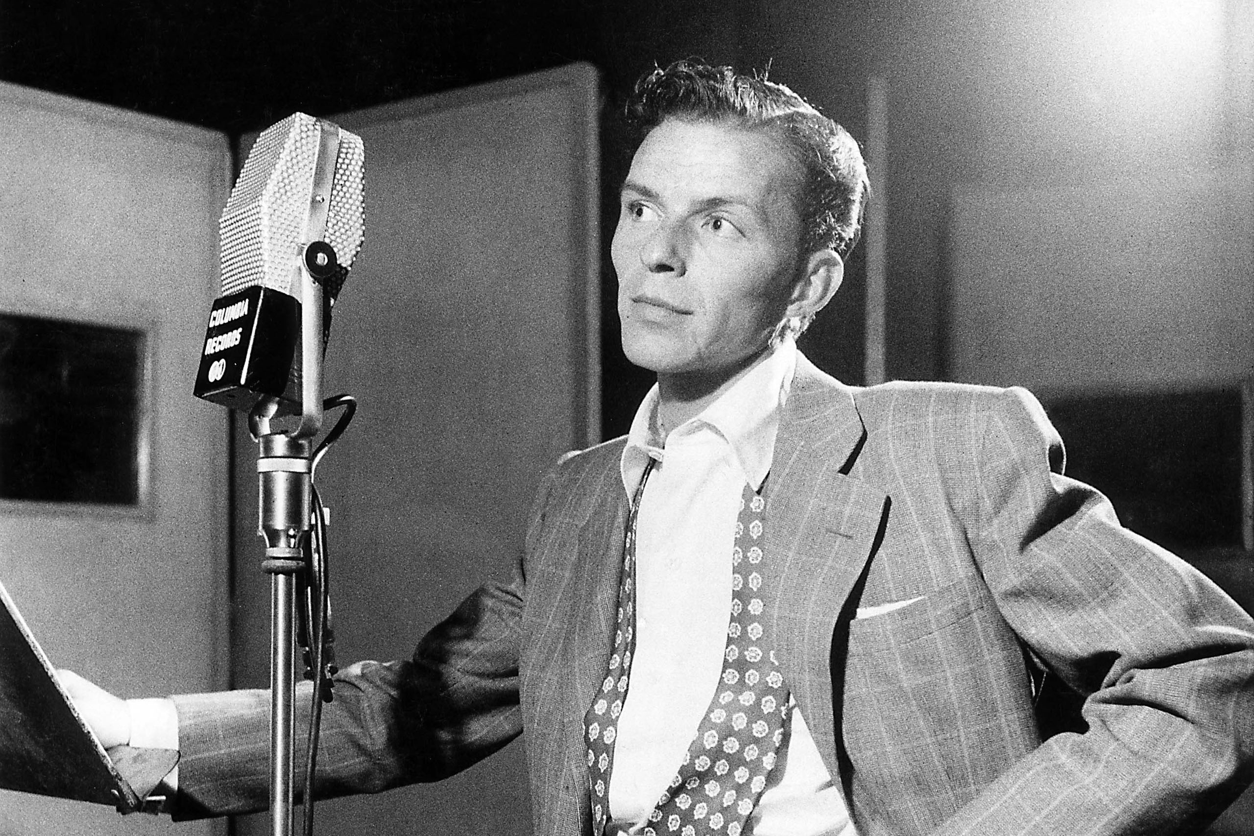 Frank Sinatra next to microphone recording at Columbia Recording studios, Liederkrantz Hall.
