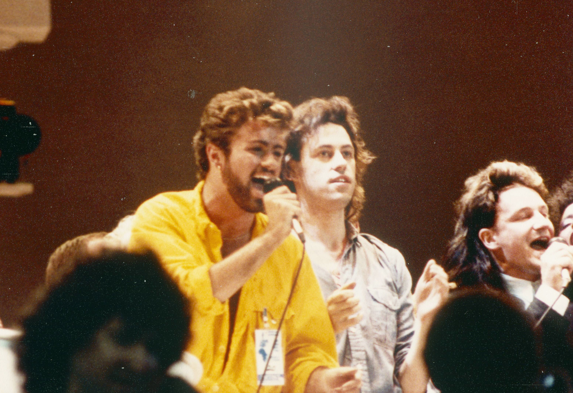 George Michael performs with Bob Geldof and Bono as part of Live Aid in London, on July 13, 1985.