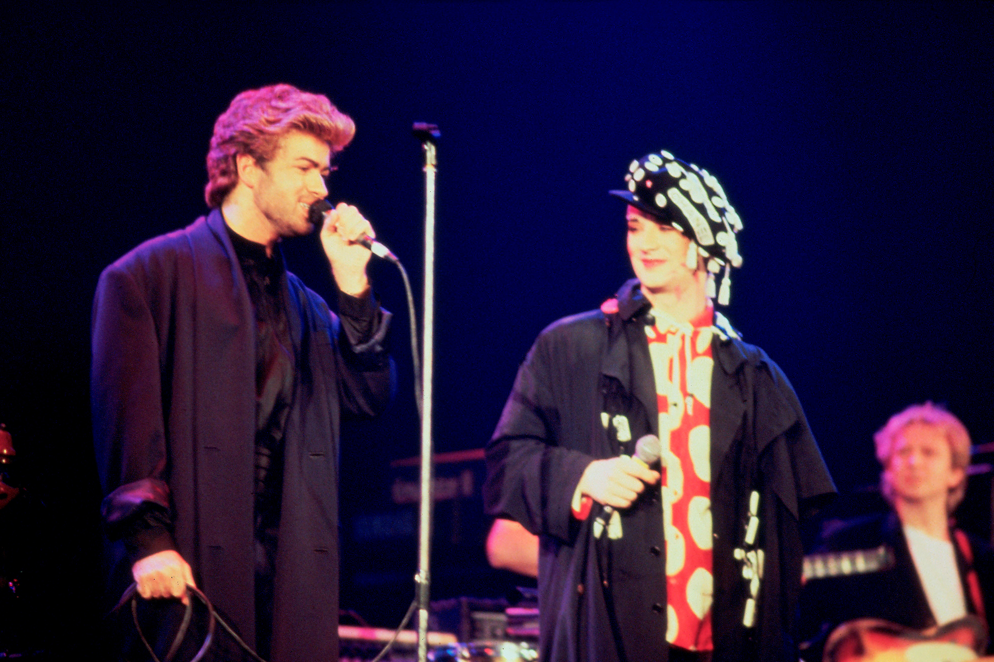George Michael performs with Boy George and The Police's Andy Summers at an AIDS awareness concert in London, April 1987.