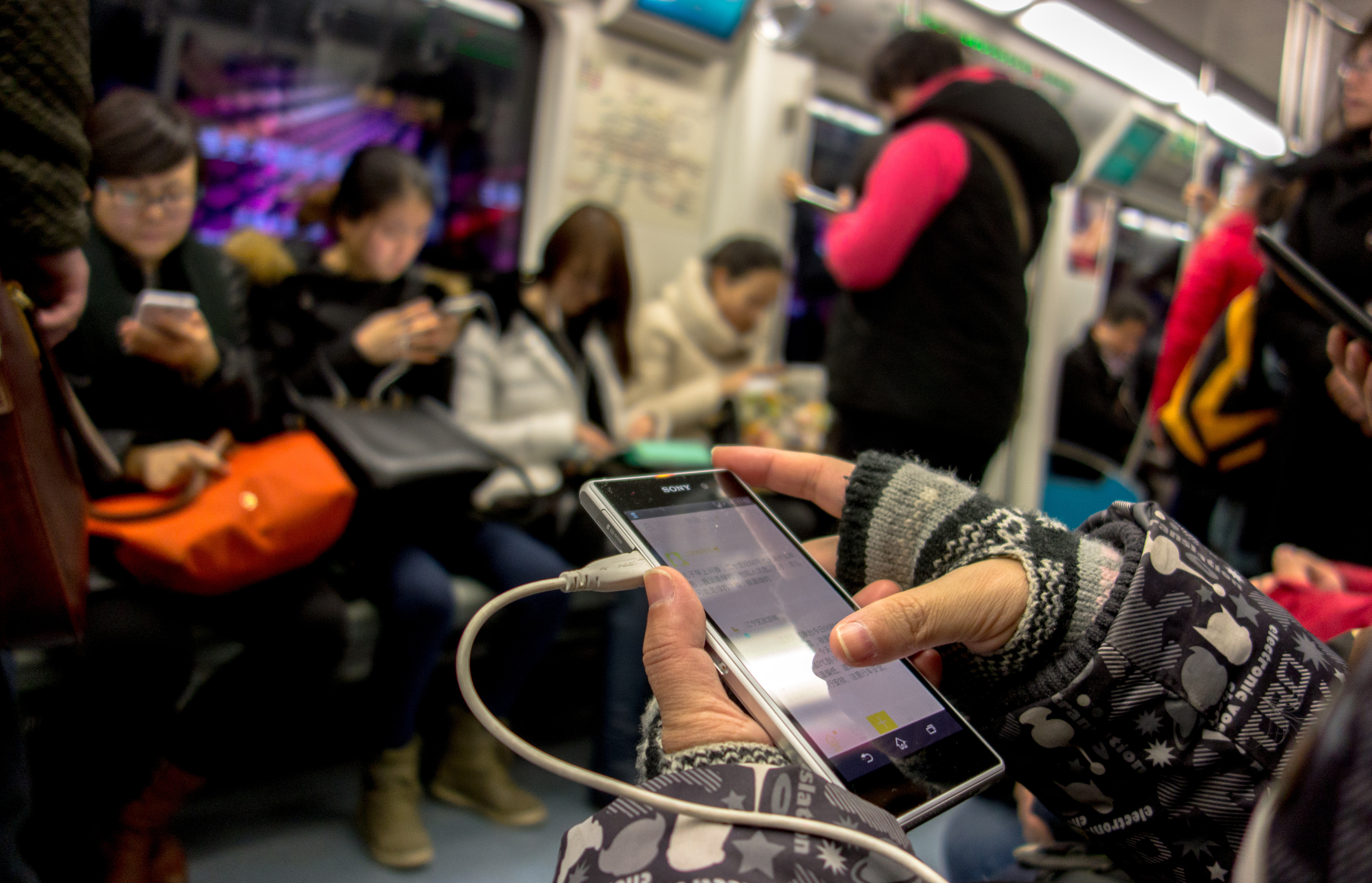 Passengers read news or watch videos on their smart phones in the subway on Jan. 28, 2015.