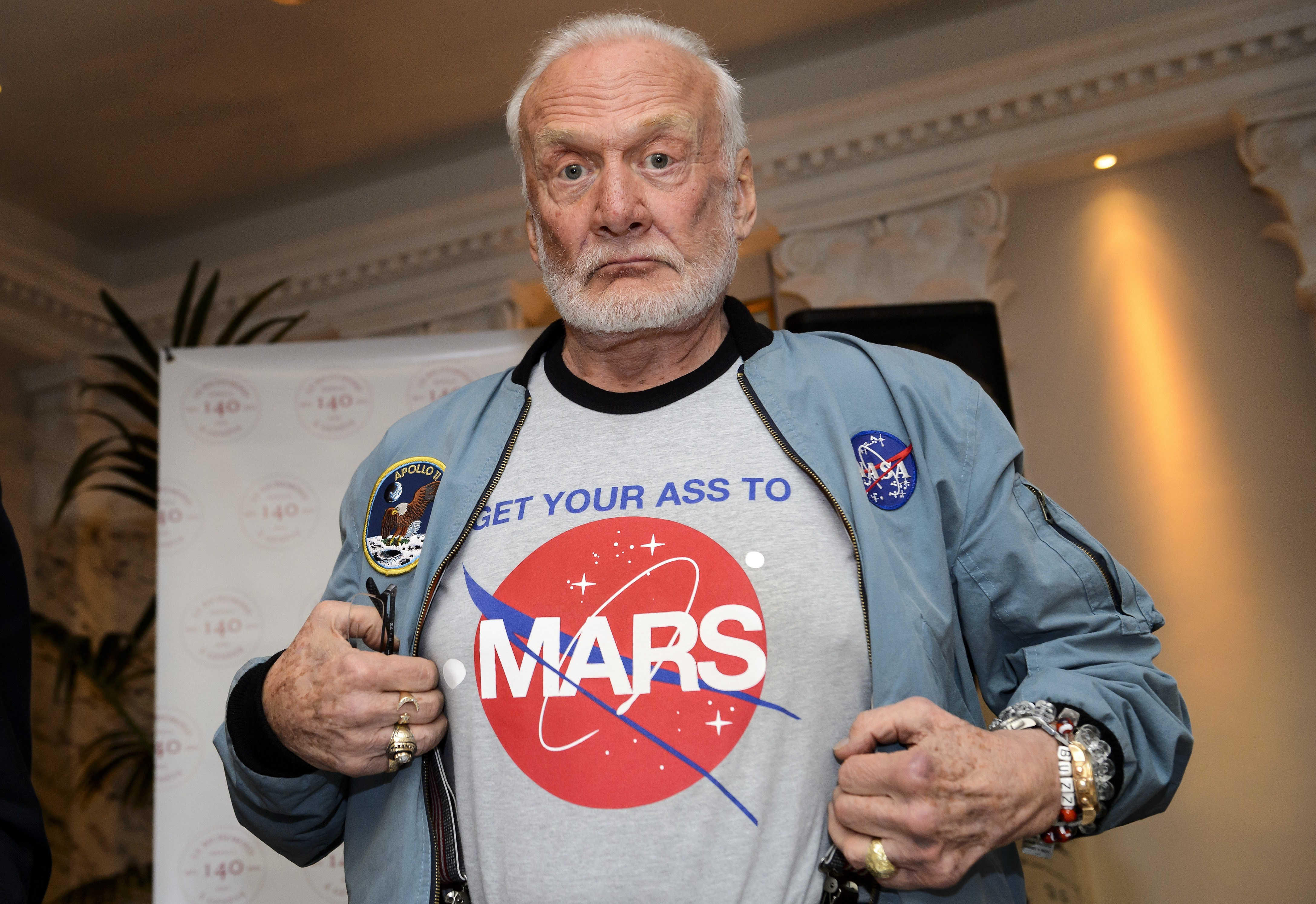 Former NASA astronaut Buzz Aldrin shows the T-shirt he wears promoting Mars exploration on Nov. 12, 2015, in Geneva
