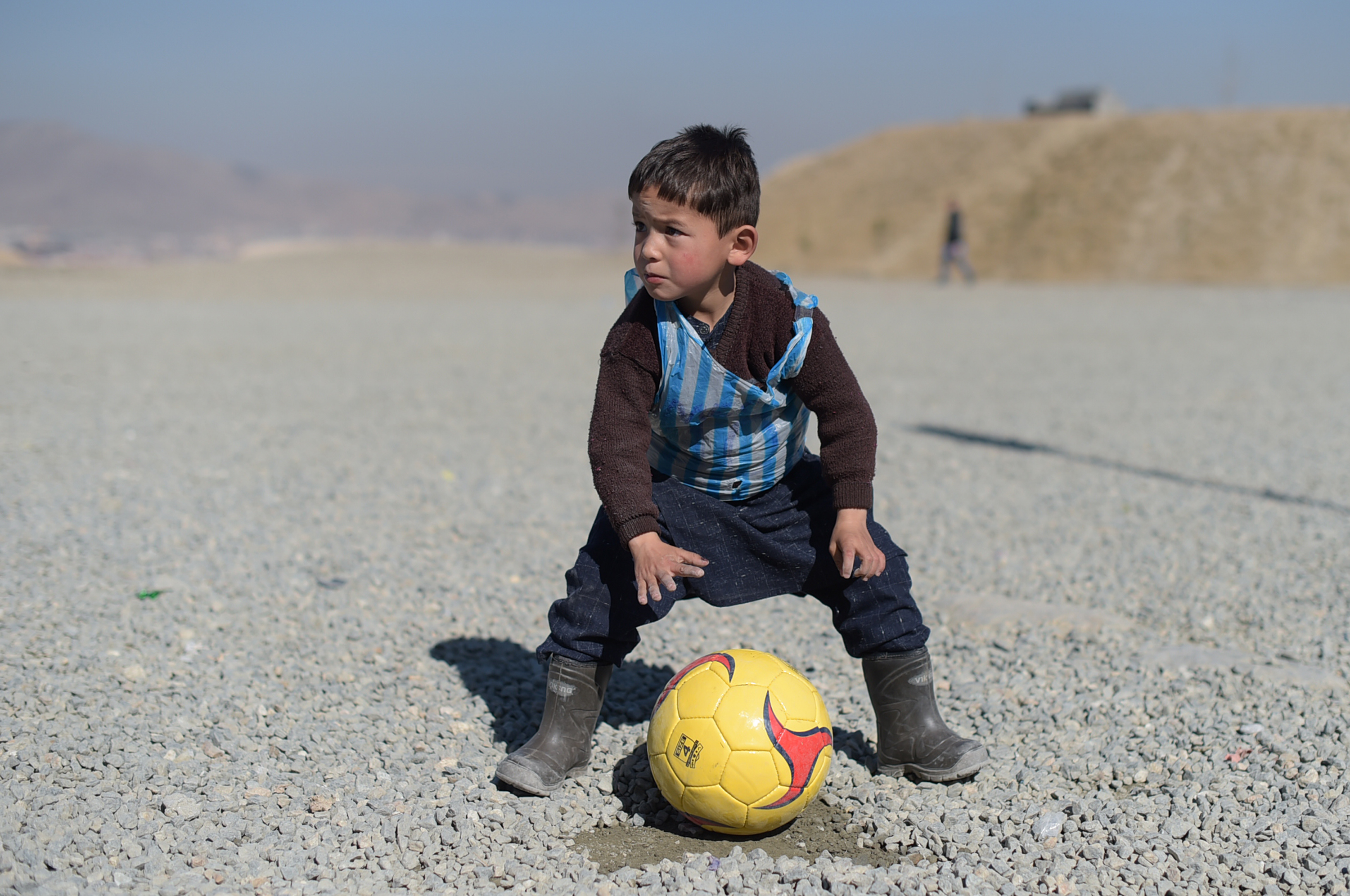 Murtaza Ahmadi, a young Lionel Messi fan, plays football in Kabul on Feb. 1, 2016