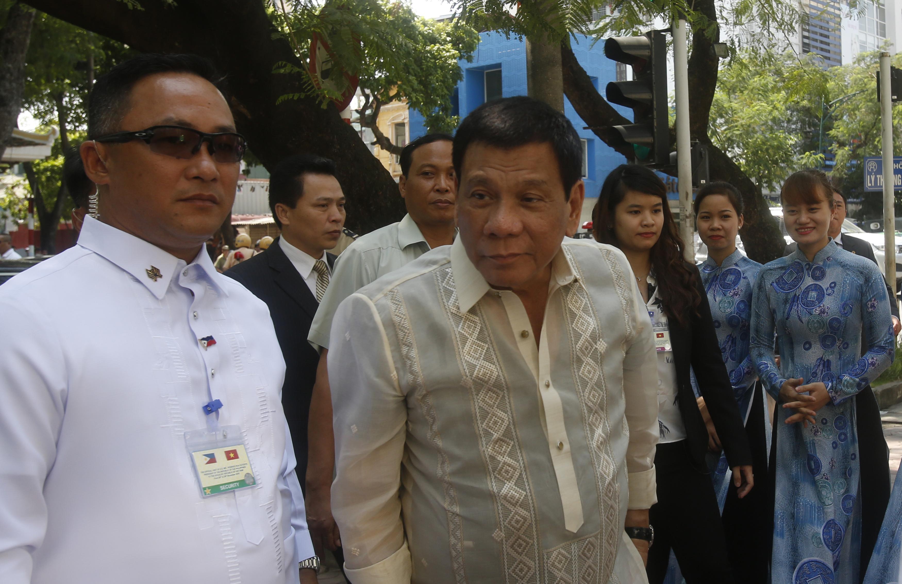 Philippine President Rodrigo Duterte (C) faces the media on his arrival at a restaurant for lunch in Hanoi on September 29, 2016.