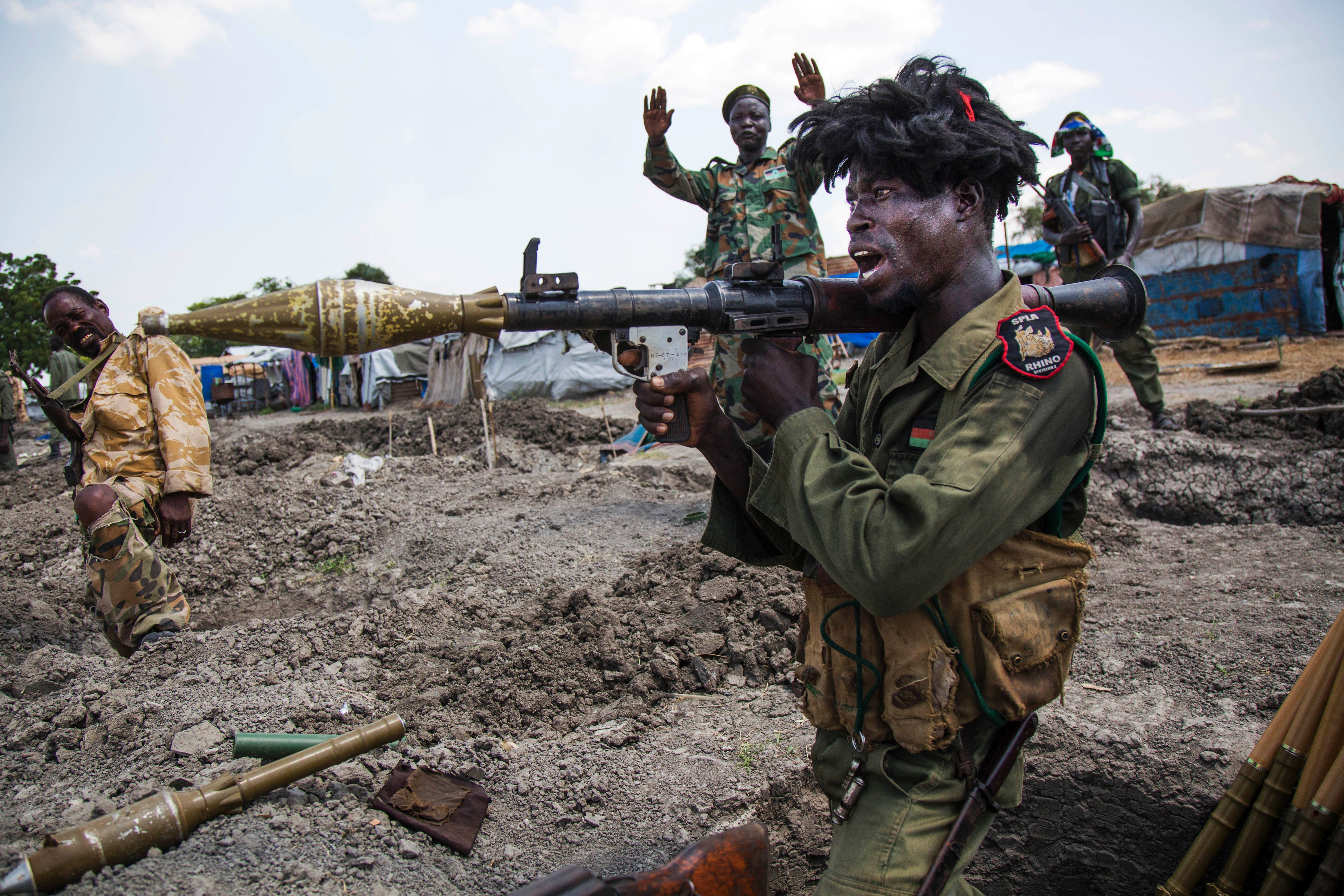 Soldiers of the Sudan People Liberation Army (SPLA) celebrate while standing in trenches in Lelo, outside Malakal, in northern South Sudan, on Oct. 16, 2016