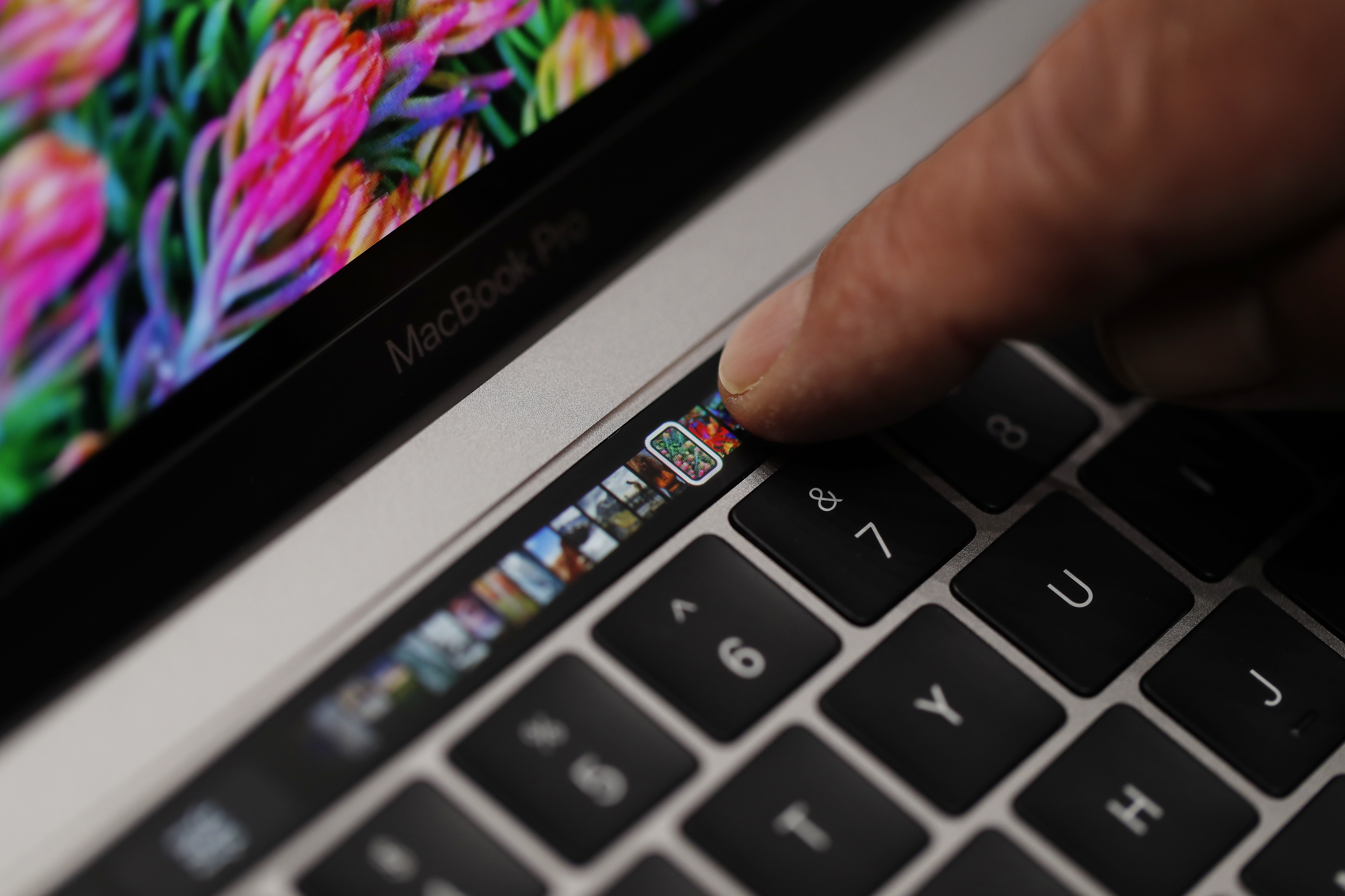 An Apple employee points to the Touch Bar on a new Apple MacBook Pro laptop during a product launch event on October 27, 2016 in Cupertino, California.