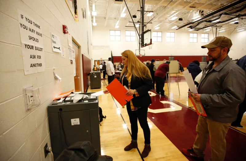A woman places her ballot in the tabulation machine after voting at Western High School  School in the US presidential election on November 8, 2016 in Detroit, Michigan.      (JEFF KOWALSKY--AFP/Getty Images)