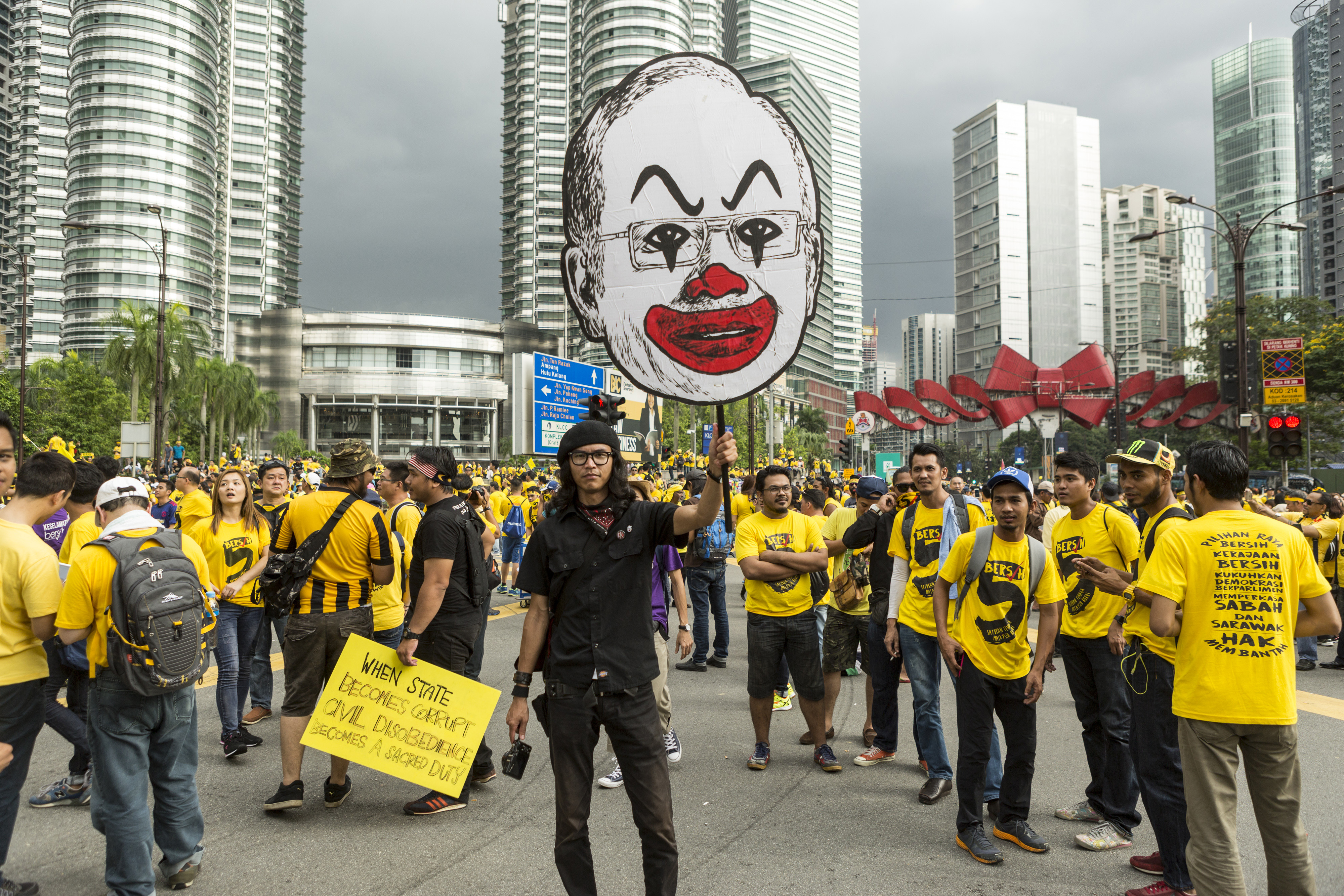 A protester holds up a placard near the Petronas Twin Towers during the Coalition for Clean and Fair Elections rally, also known as Bersih, in Kuala Lumpur on Nov. 19, 2016