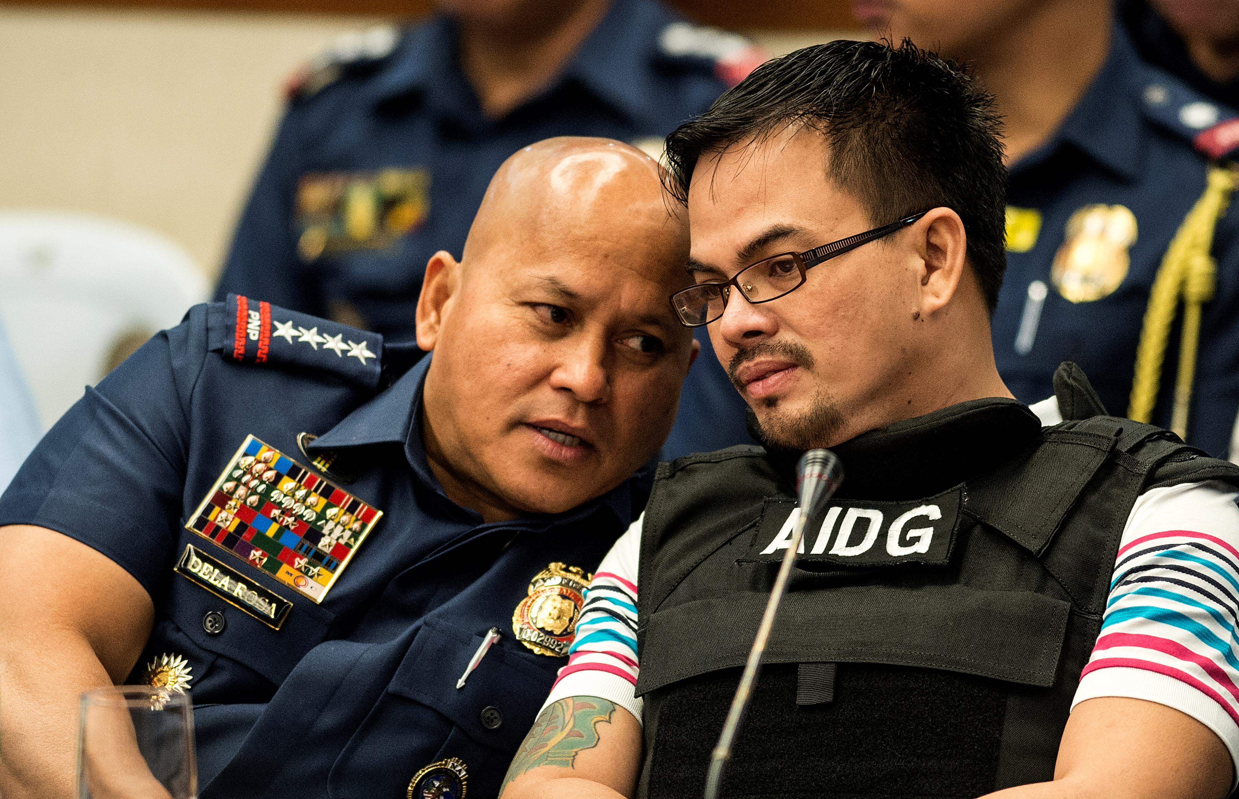 The Philippines' police chief Ronald dela Rosa, left, talks to Kerwin Espinosa son of the late Albuera Mayor Rolando Espinosa at the Senate building in Manila on Nov. 23, 2016