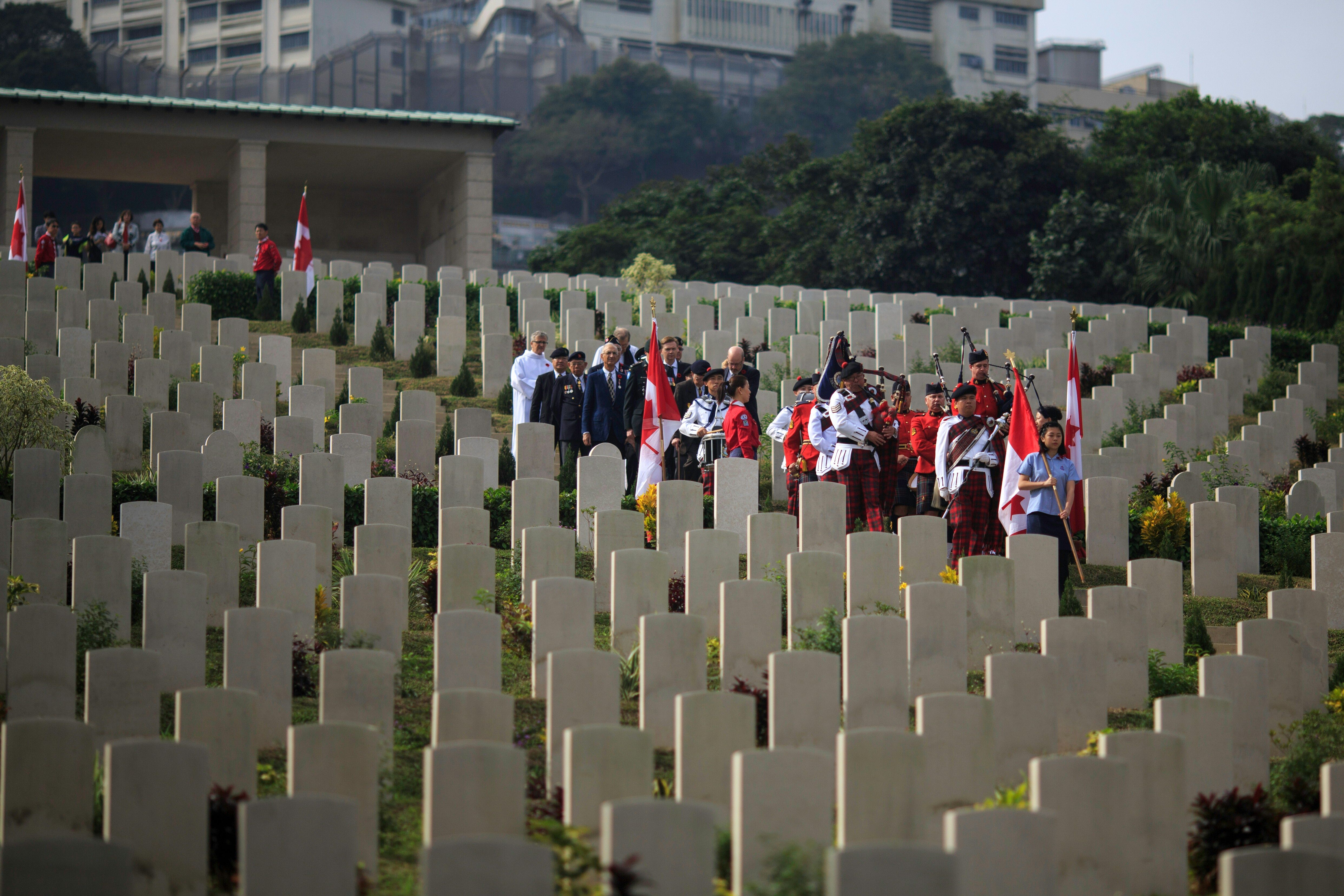 A pipes-and-drum band, comprising members of the Hong Kong Police and Royal Canadian Mounted Police, leads a procession past tombstones in Hong Kong's Sai Wan War Cemetery on Dec. 4, 2016, during the Canadian commemorative ceremony honoring those who died during the Battle of Hong Kong and World War II