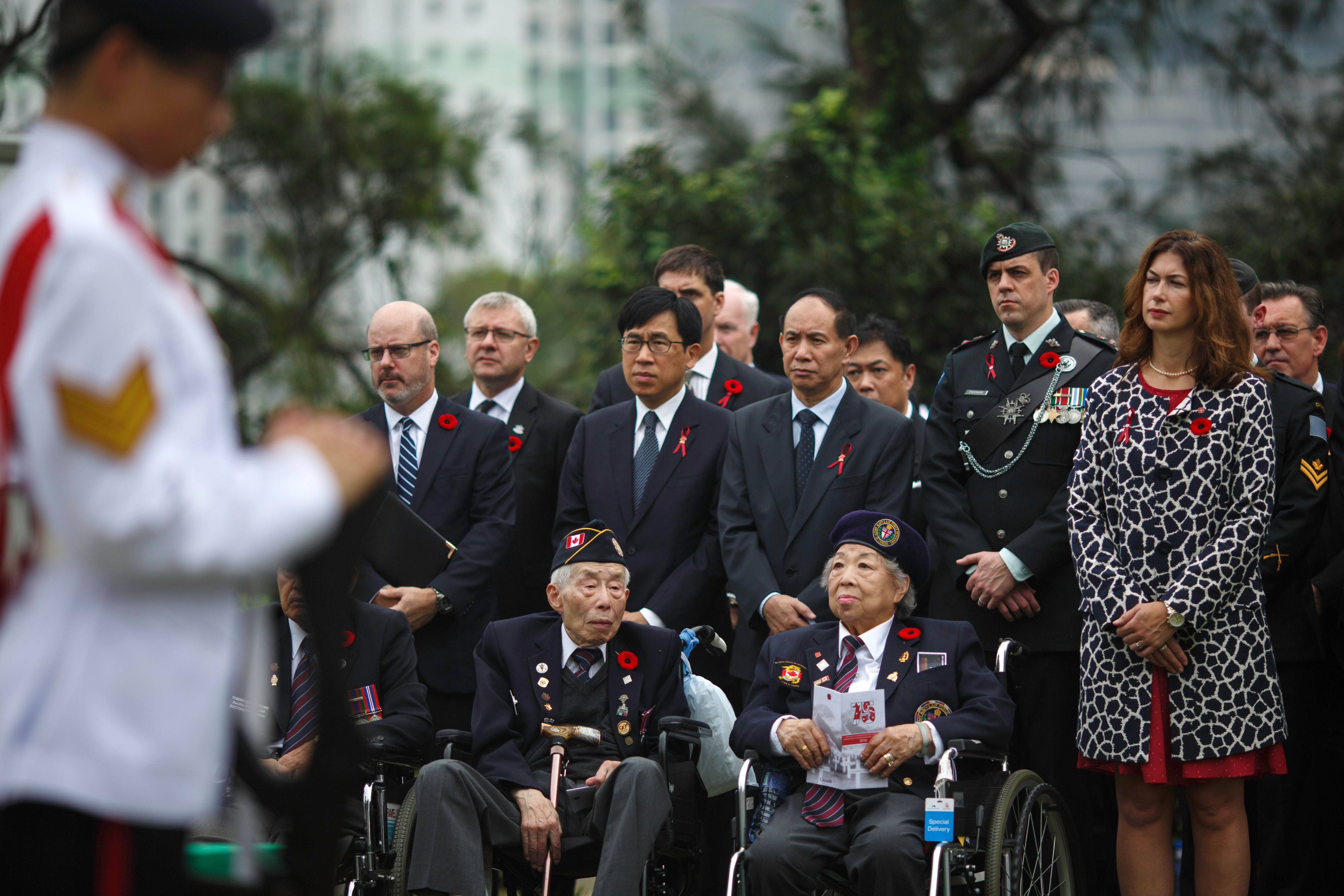 Hong Kong World War II veterans, front row, and attendees, including relatives of World War II veterans, attend the Canadian commemorative ceremony in Hong Kong's Sai Wan War Cemetery on Dec. 4, 2016, honoring those who died during the Battle of Hong Kong and World War II