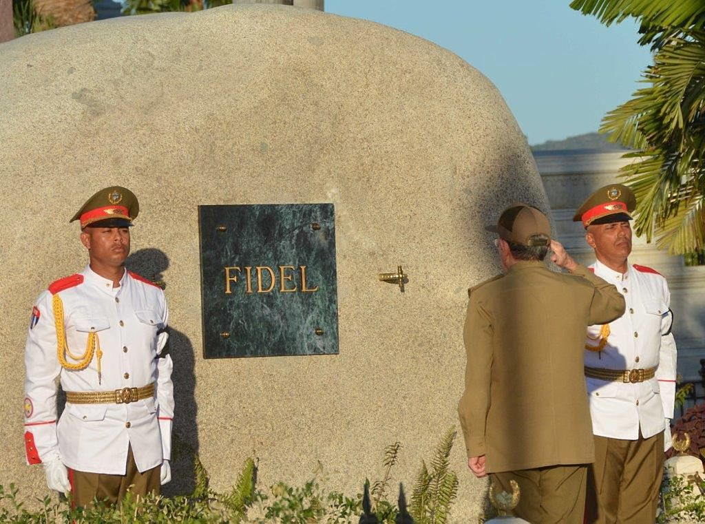 Cuban President Raul Castro salutes for the last time his brother Fidel Castro after placing the urn with his ashes in his tomb at the Santa Ifigenia cemetery in Santiago de Cuba on December 4, 2016.                     Fidel Castro's ashes were buried alongside national heroes in the cradle of his revolution on Sunday, as Cuba opens a new era without the communist leader who ruled the island for decades. / AFP / AIN / Marcelino VAZQUEZ        (Photo credit should read MARCELINO VAZQUEZ/AFP/Getty Images)