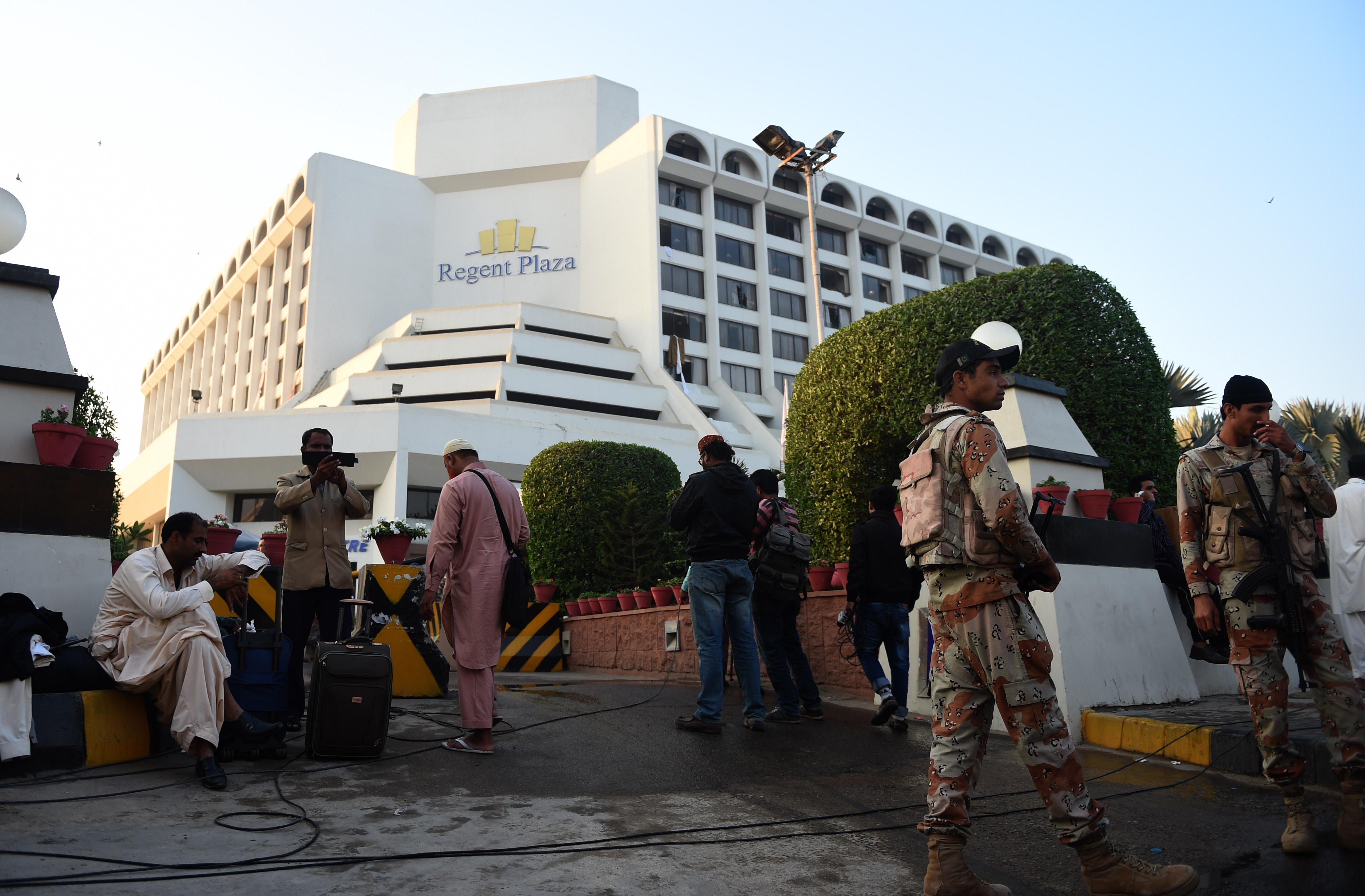 Guests gather outside the Regent Plaza Hotel following a fire in the building, located in Pakistan's port city of Karachi, on Dec. 5, 2016