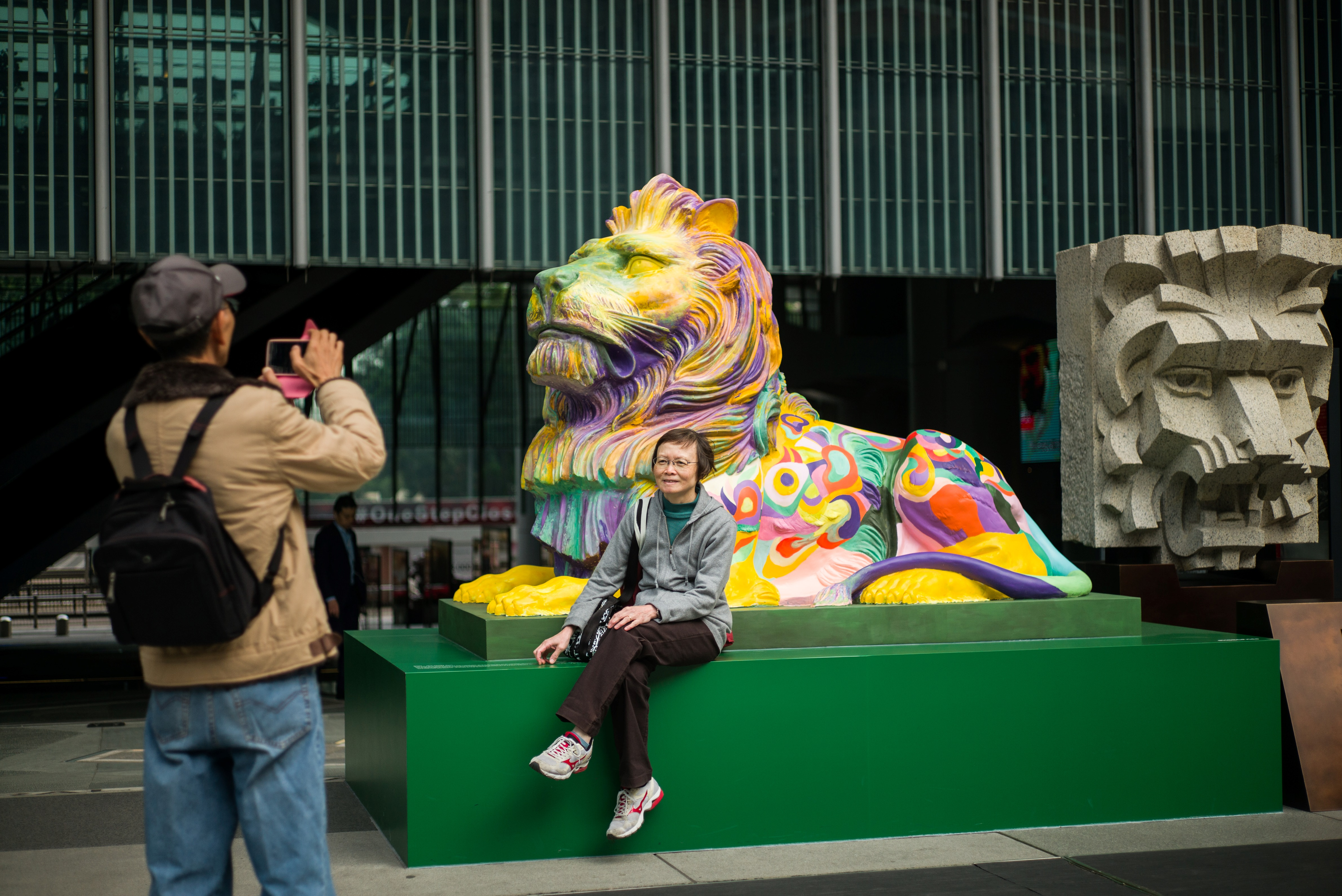 A man takes a photo of his wife as she poses in front of a lion painted in rainbow stripes outside HSBC's main office in Hong Kong on Dec. 6, 2016