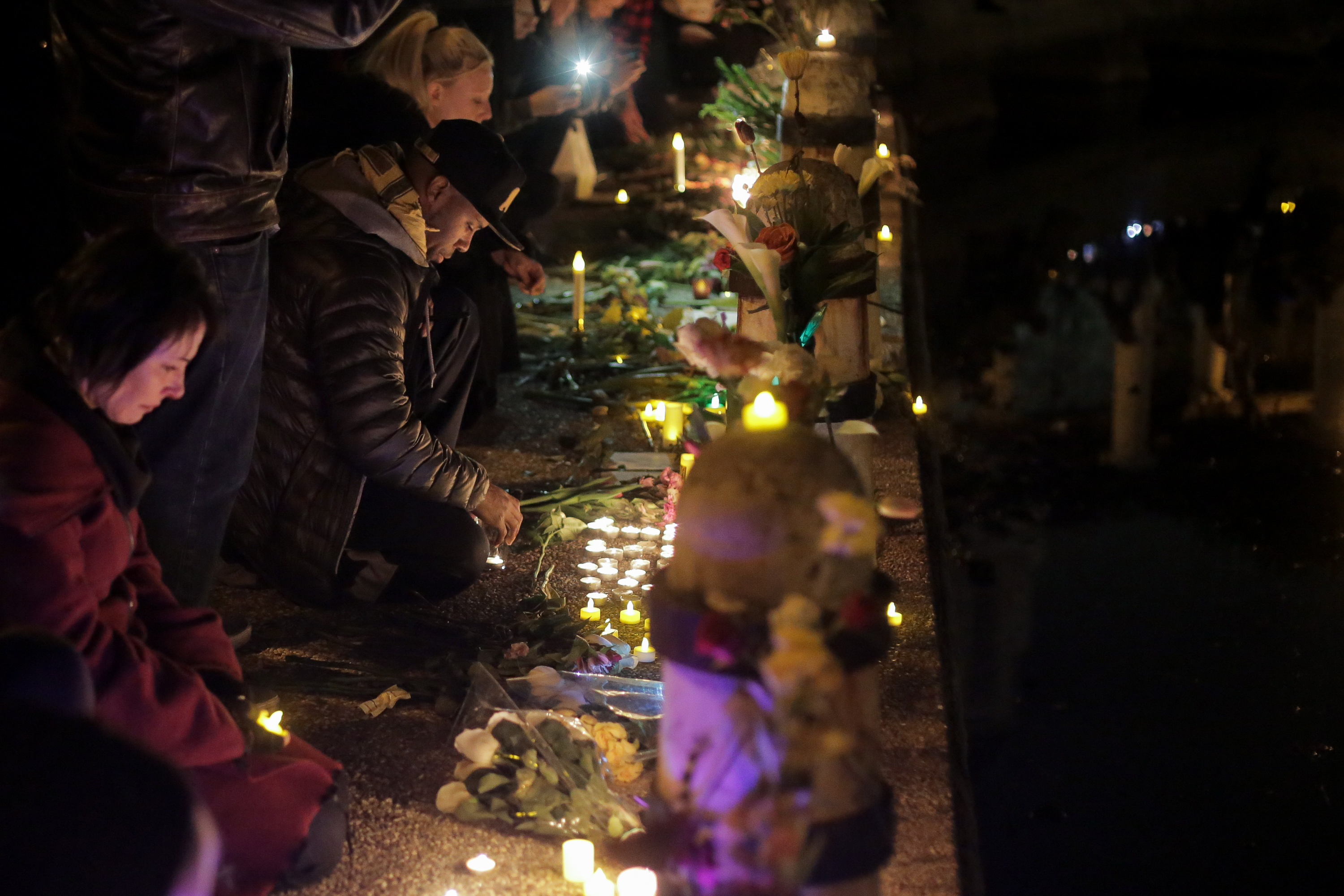 A man lights a candle at a vigil for the victims of a warehouse fire that has claimed the lives of at least thirty-six people on December 5, 2016 in Oakland, California.