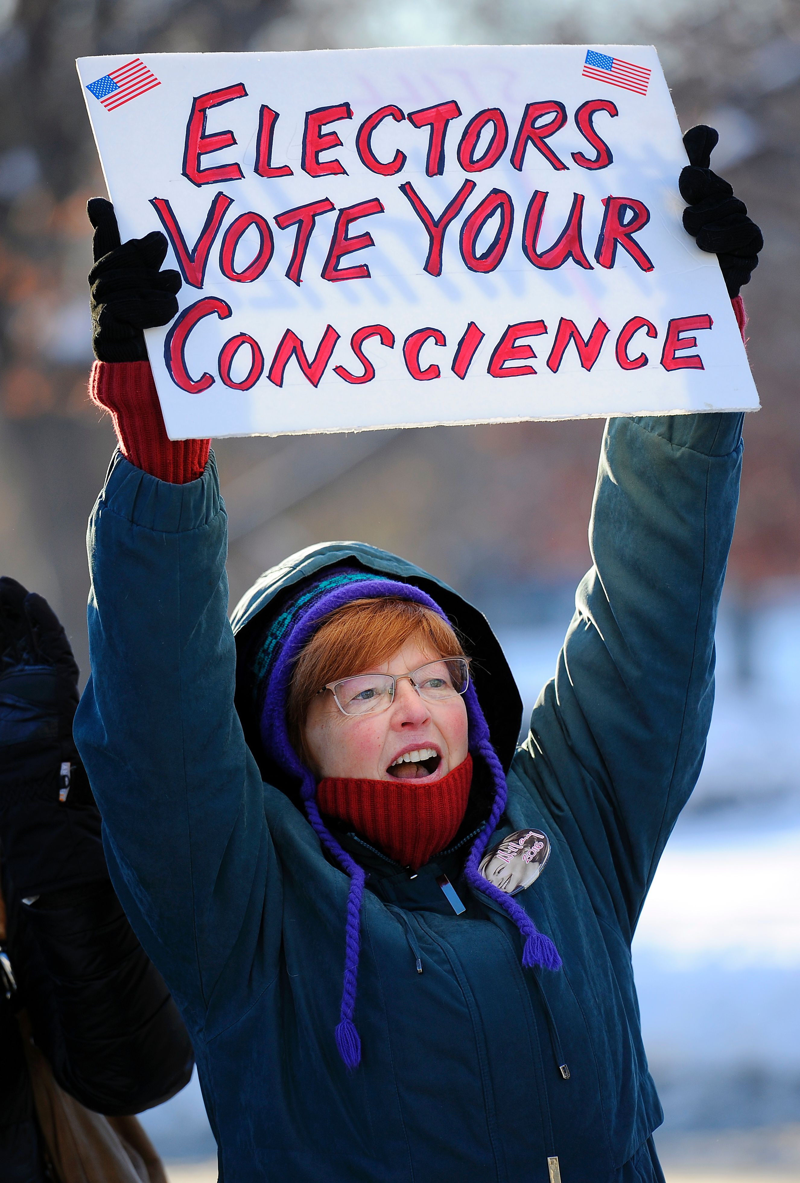Gloria McVeigh, 65, holds a sign and cheers during a demonstration against US President-elect Donald Trump on the eve of the Electoral College vote, in Denver, Colorado on December 18, 2016. AFP—AFP/Getty Images