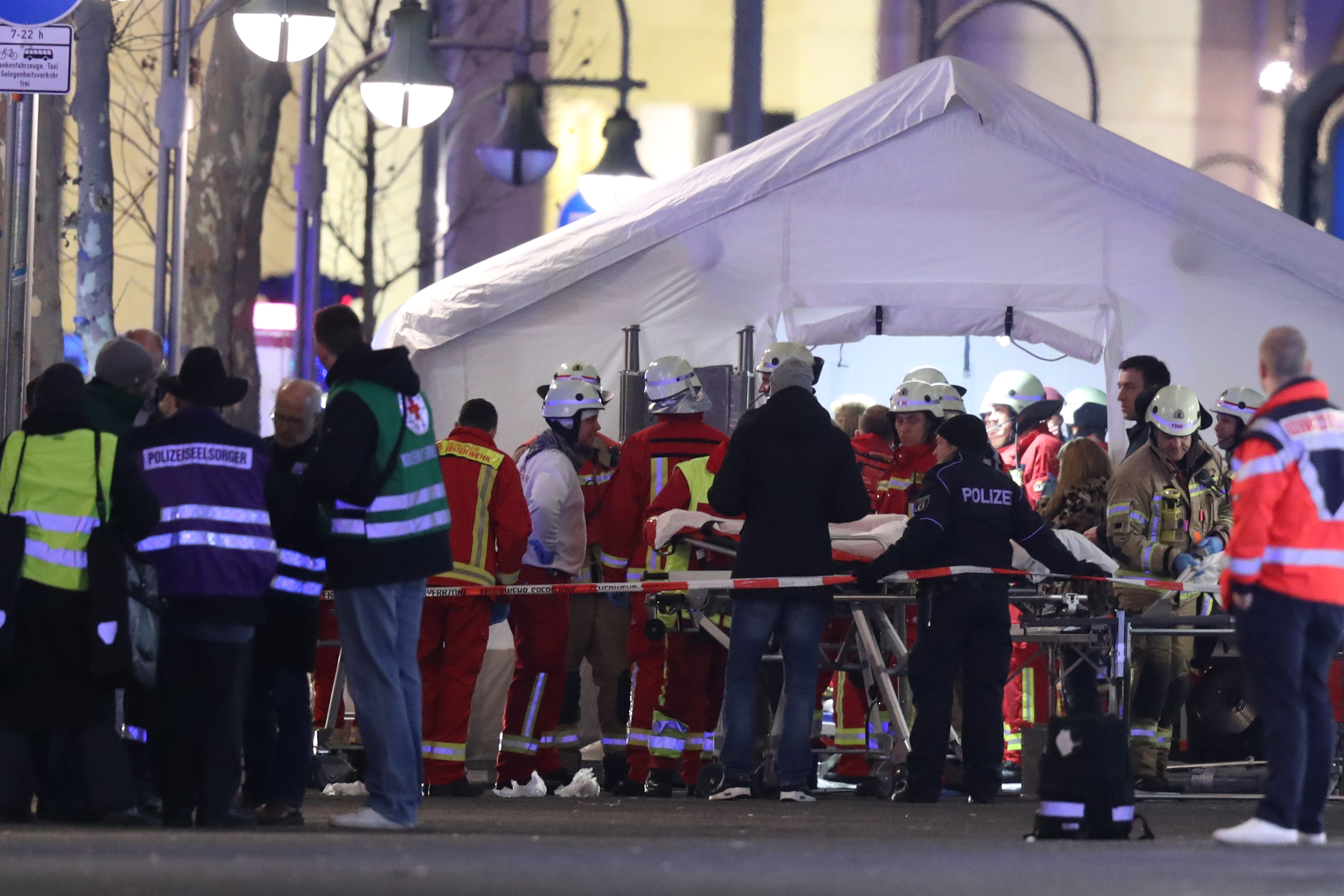 Rescue workers gather with stretchers outside a tent in the area after a lorry plowed through a Christmas market on December 19, 2016 in Berlin, Germany.
