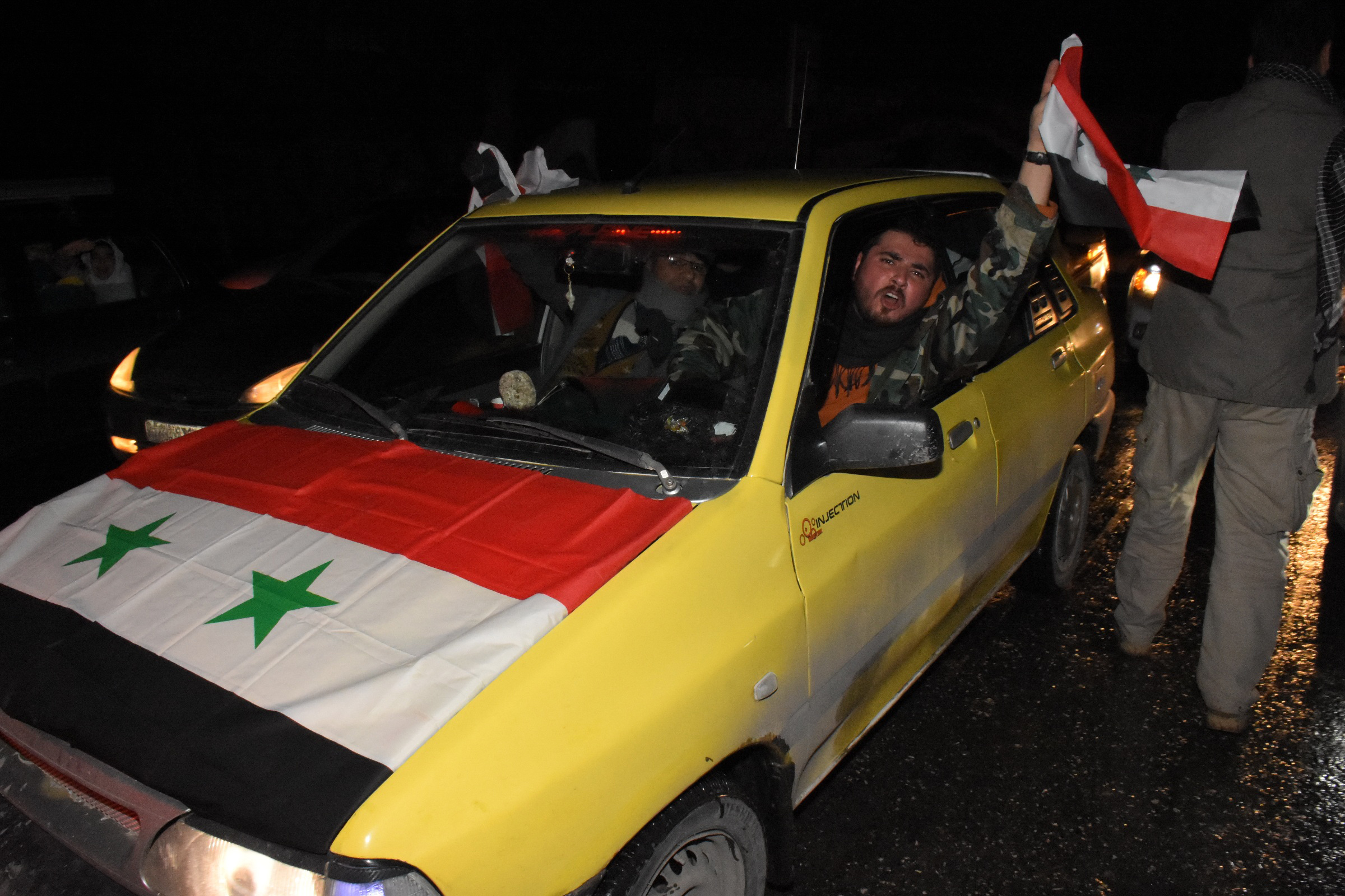 A Syrian driver flies a national flag as people celebrate in the streets on December 22, 2016 in the northern Syrian city of Aleppo, after the army said it regained full control of the country's second city.