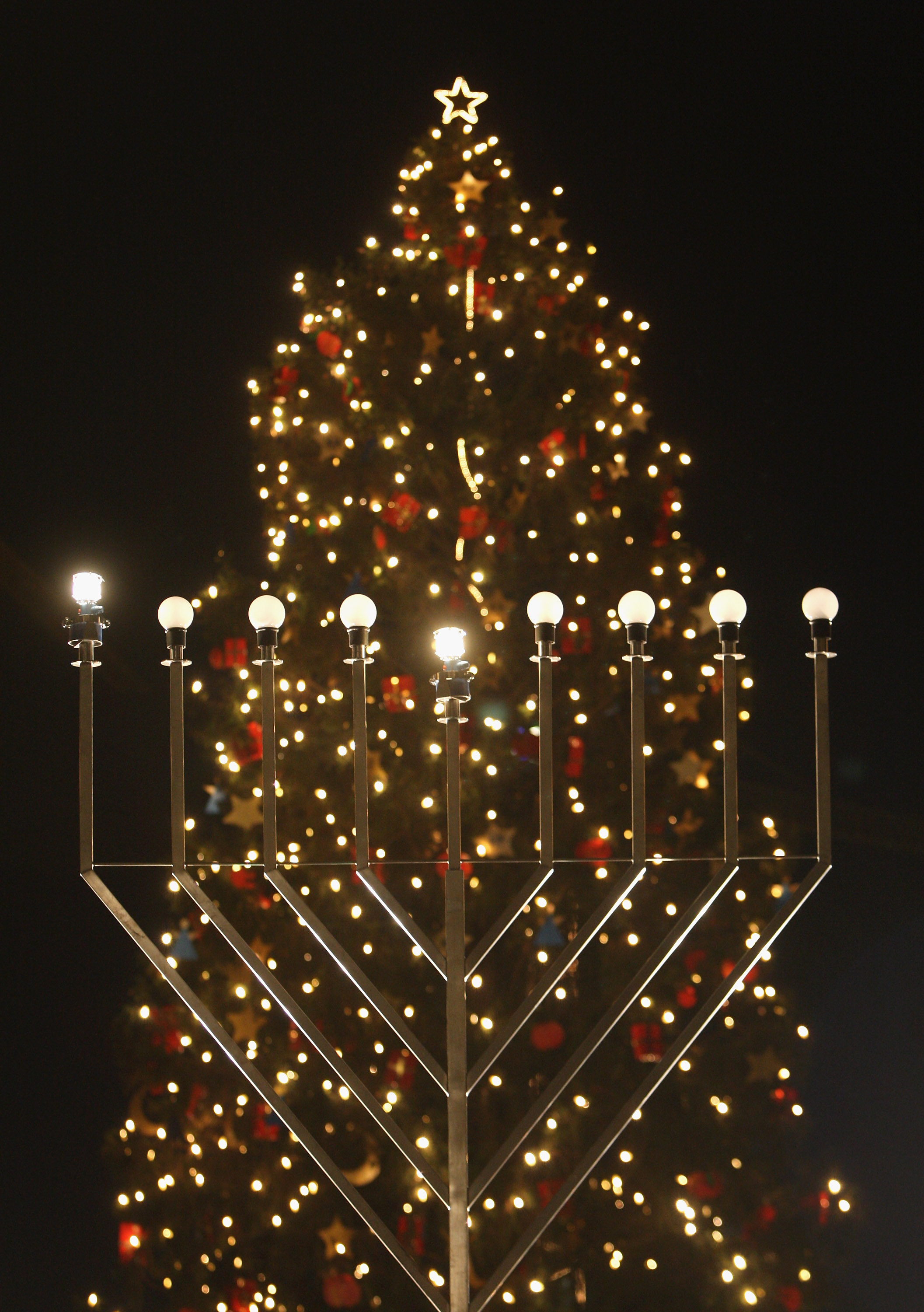 A giant, gas-lit menorah stands in front of a Christmas tree shortly after members of the local Jewish community lit the menorah on the night before the first day of Hannukah on Dec. 4, 2007 in Berlin, Germany.