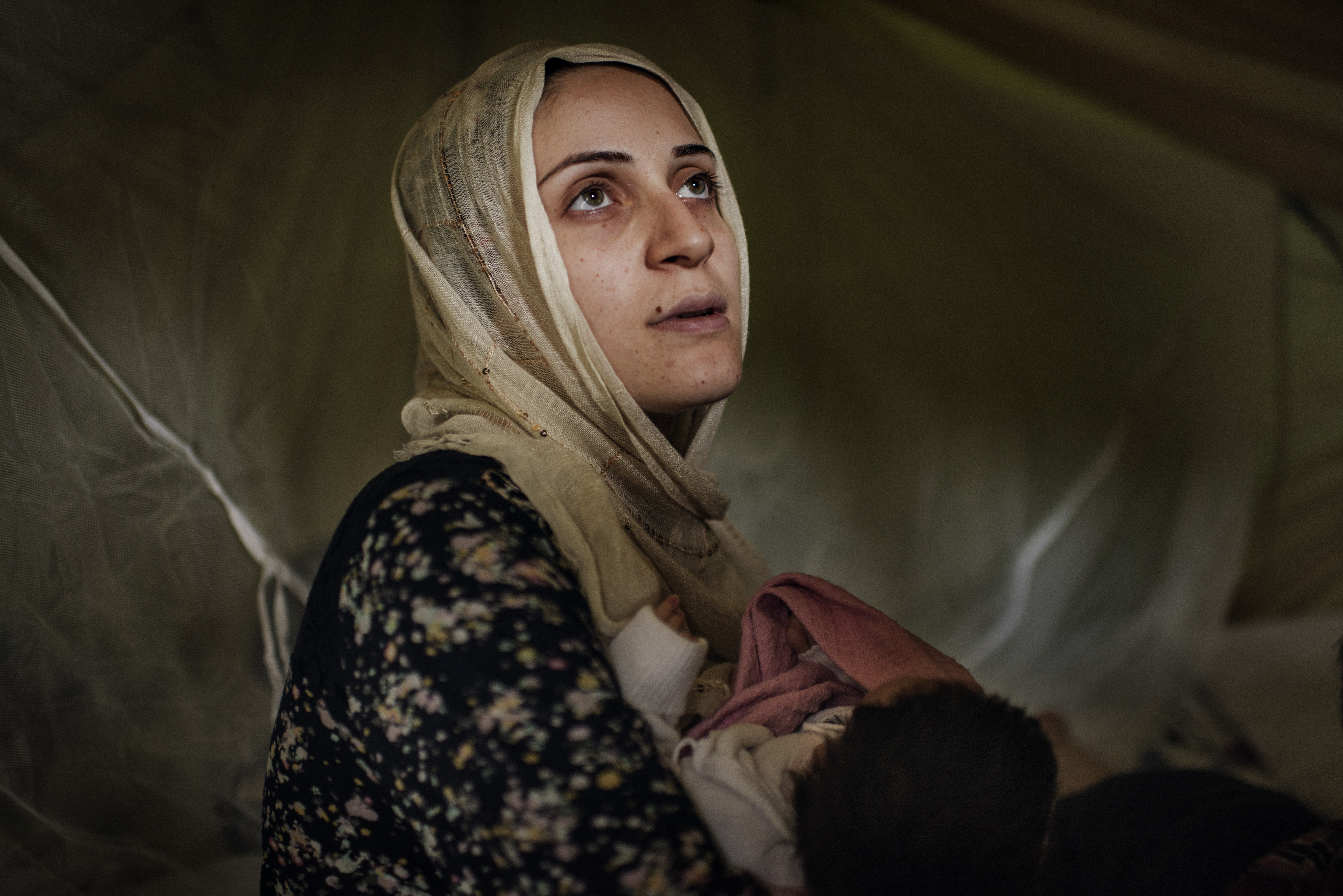 Taimma Abazli, 24, holds her new baby Heln in their tent at the Karamalis camp in Thessaloniki, Greece, September 2016.