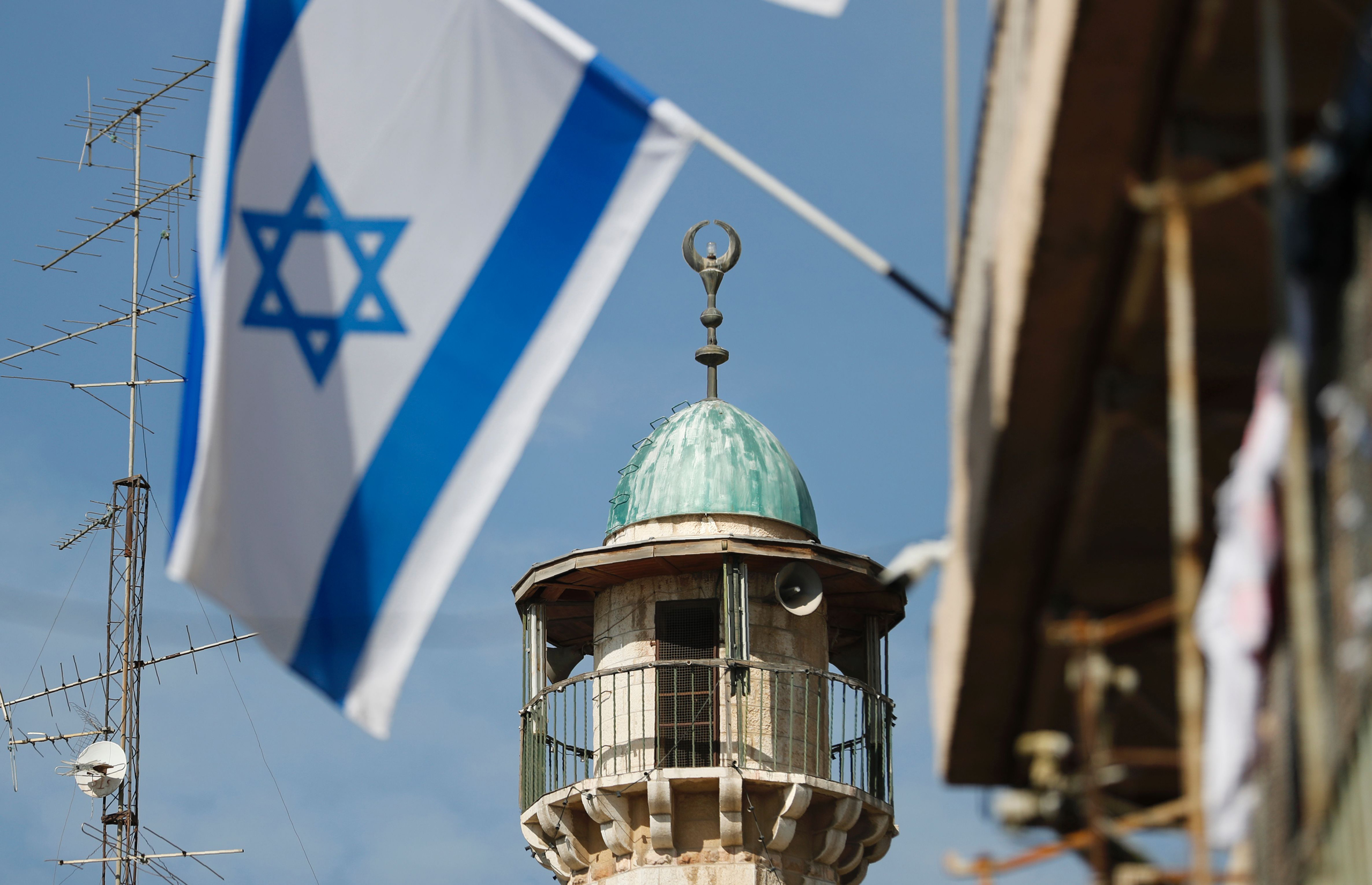 An Israeli flag waves in front of a mosque in the Arab quarter of Jerusalem's Old City on November 14, 2016. Israeli Prime Minister Benjamin Netanyahu said he backed a bill limiting the volume of calls to prayer from mosques, a proposal critics have called a threat to religious freedom.