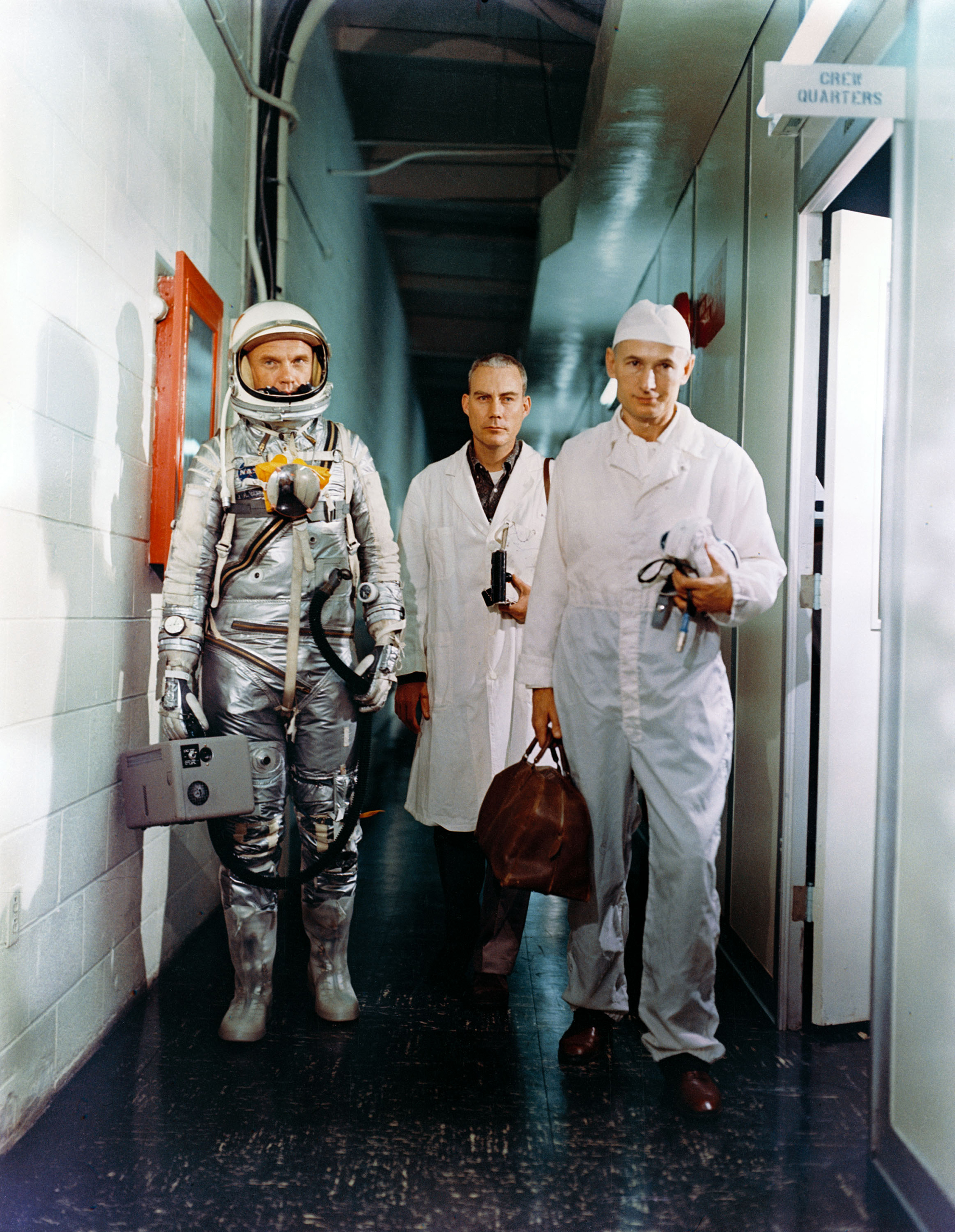 <b>Suited Up</b> Glenn's walk into history began in an unprepossessing hallway as he left the crew quarters on the morning of his Feb. 20, 1962, launch in the company of a flight surgeon and an equipment specialist.