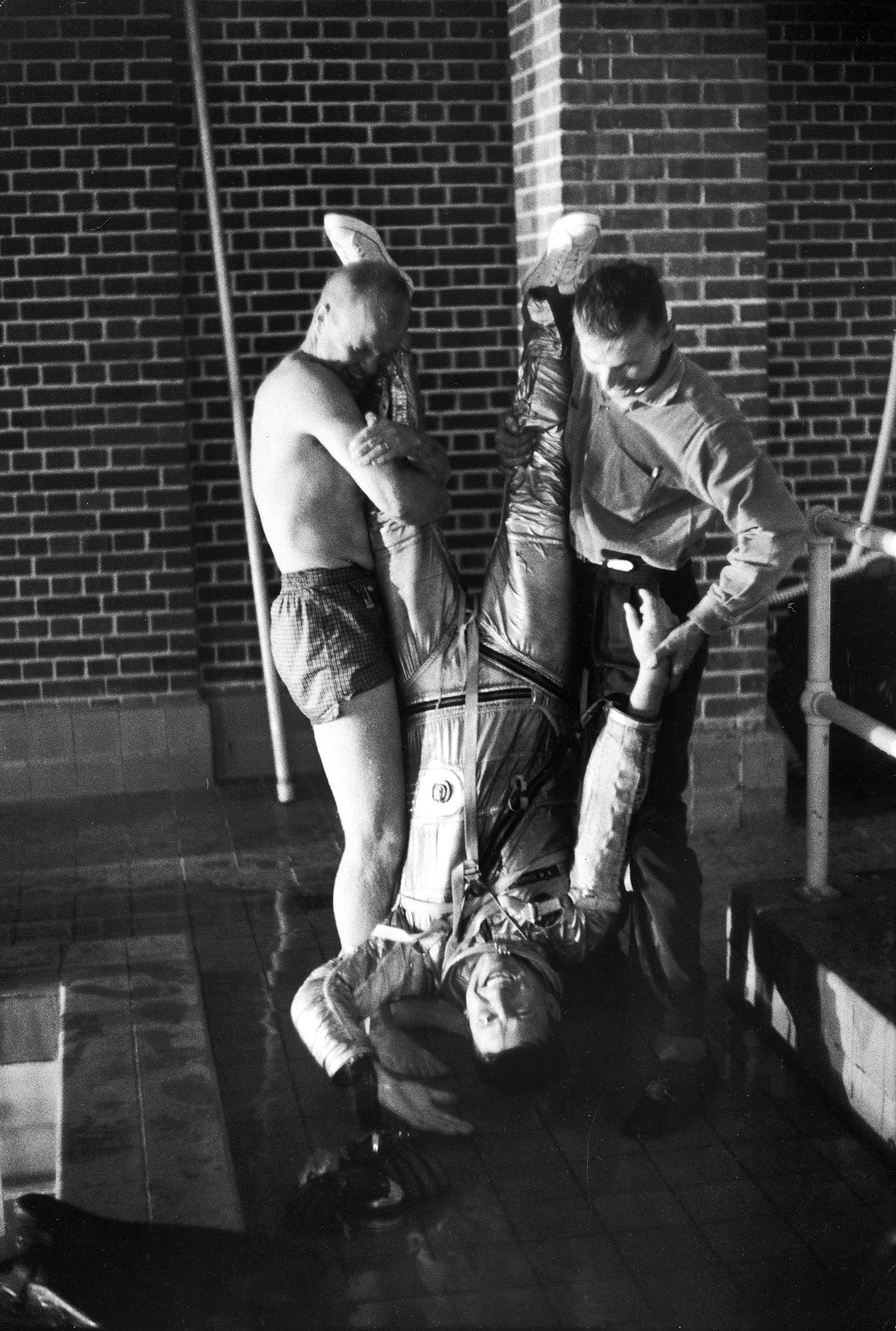 <b>A Draining Training Session</b> Glenn, left, and a NASA technician try a low-tech — but very direct — way of helping fellow astronaut Wally Schirra drain his pressure suit of water after testing it in a pool in 1960. Knowing the suit's flotation properties may have helped save the life of Gus Grissom, who wound up paddling in the Atlantic Ocean after the hatch of his spacecraft blew off following splashdown.