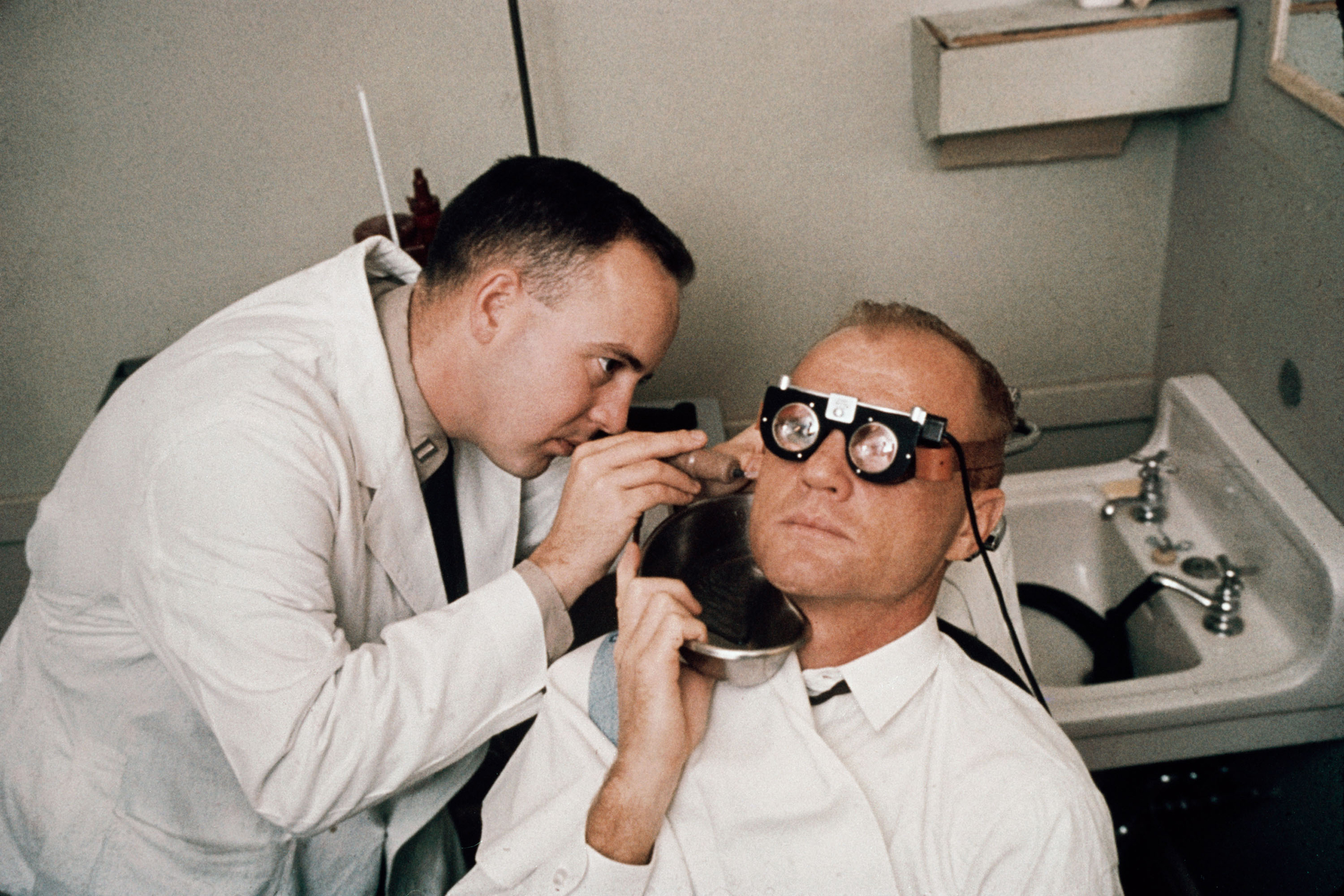 <b>Another Balance Test</b> Cold water is poured into Glenn's ear while goggles track his eye motions shortly before his 1962 flight. The water scrambles the balance system — one more test of how the astronaut would function in zero g.